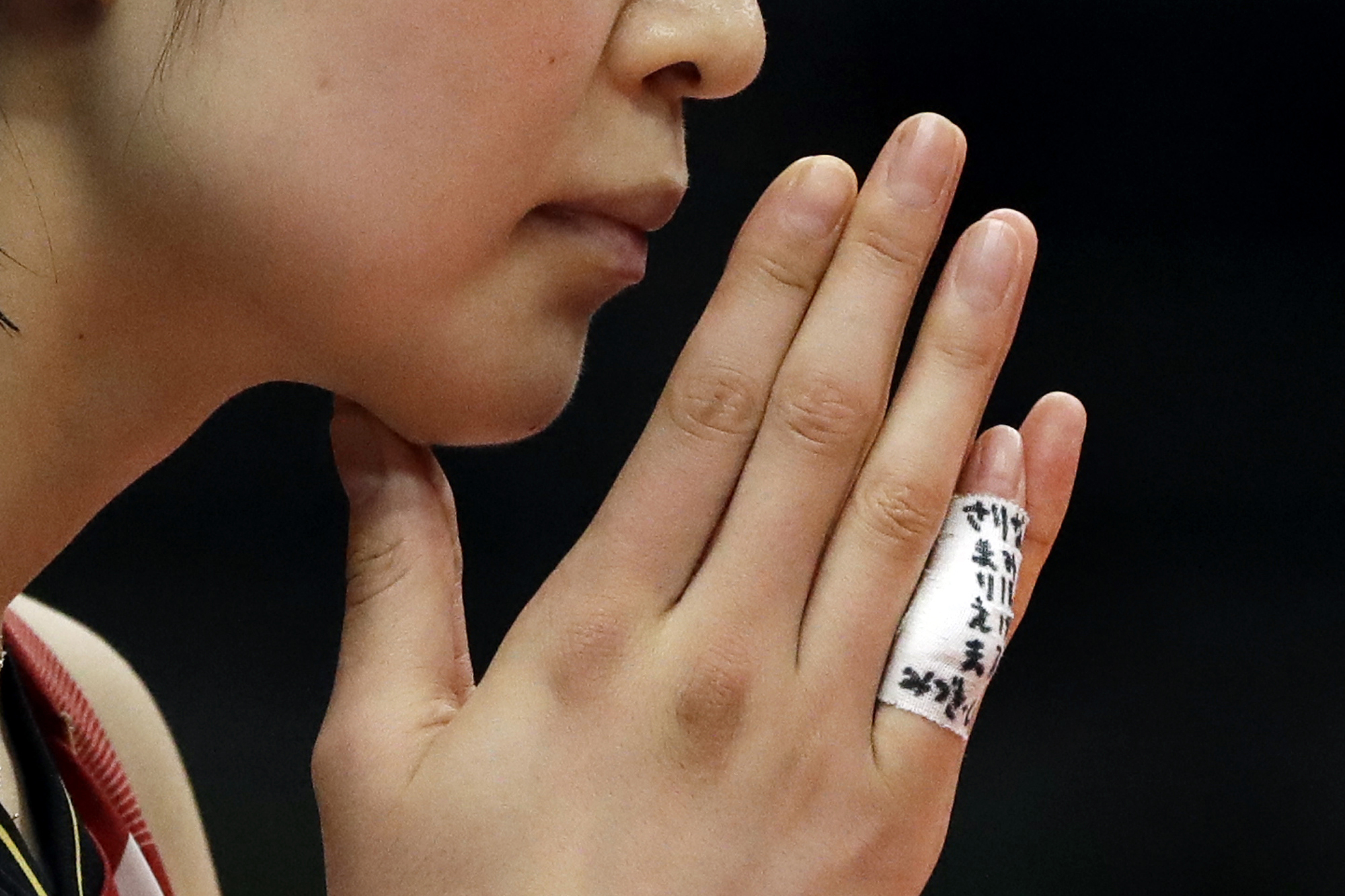 Saori Kimura raises her hand to her face as she awaits the next serve during a women's preliminary volleyball match against Argentina on Sunday at the 2016 Summer Olympics in Rio de Janeiro. The names of teammates who did not make the final Olympic roster are written on bandages on her fingers. | AP