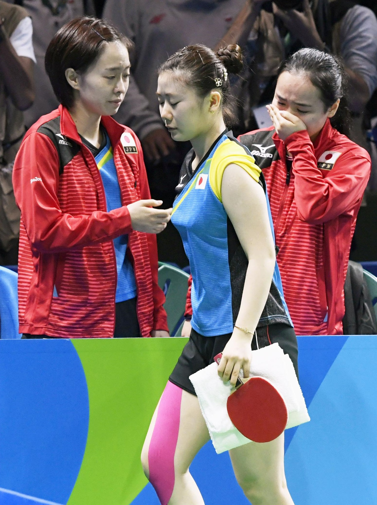 Ai Fukuhara (center) exits while teammates Kasumi Ishikawa  and Mima Ito react after losing their women's table tennis team semifinal match 3-2 to Germany at the 2016 Rio Olympics on Sunday. | KYODO
