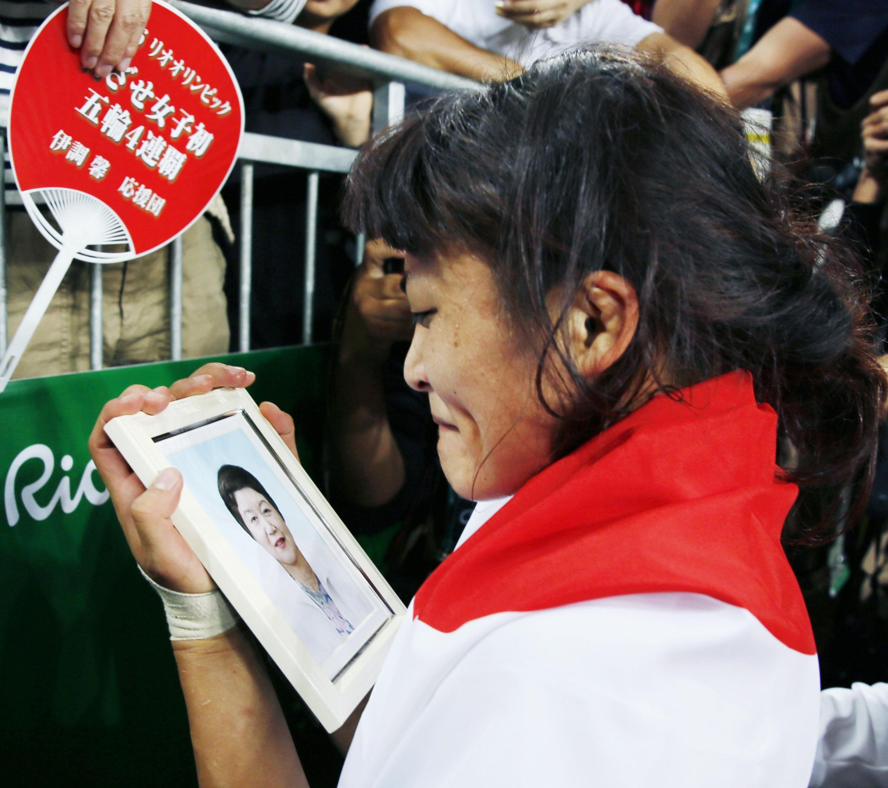 Kaori Icho looks at a picture of her late mother, Toshi, after clinching the fourth straight gold medal of the women's freestyle wrestling event on Wednesday at the 2016 Rio de Janeiro Olympics. | KYODO
