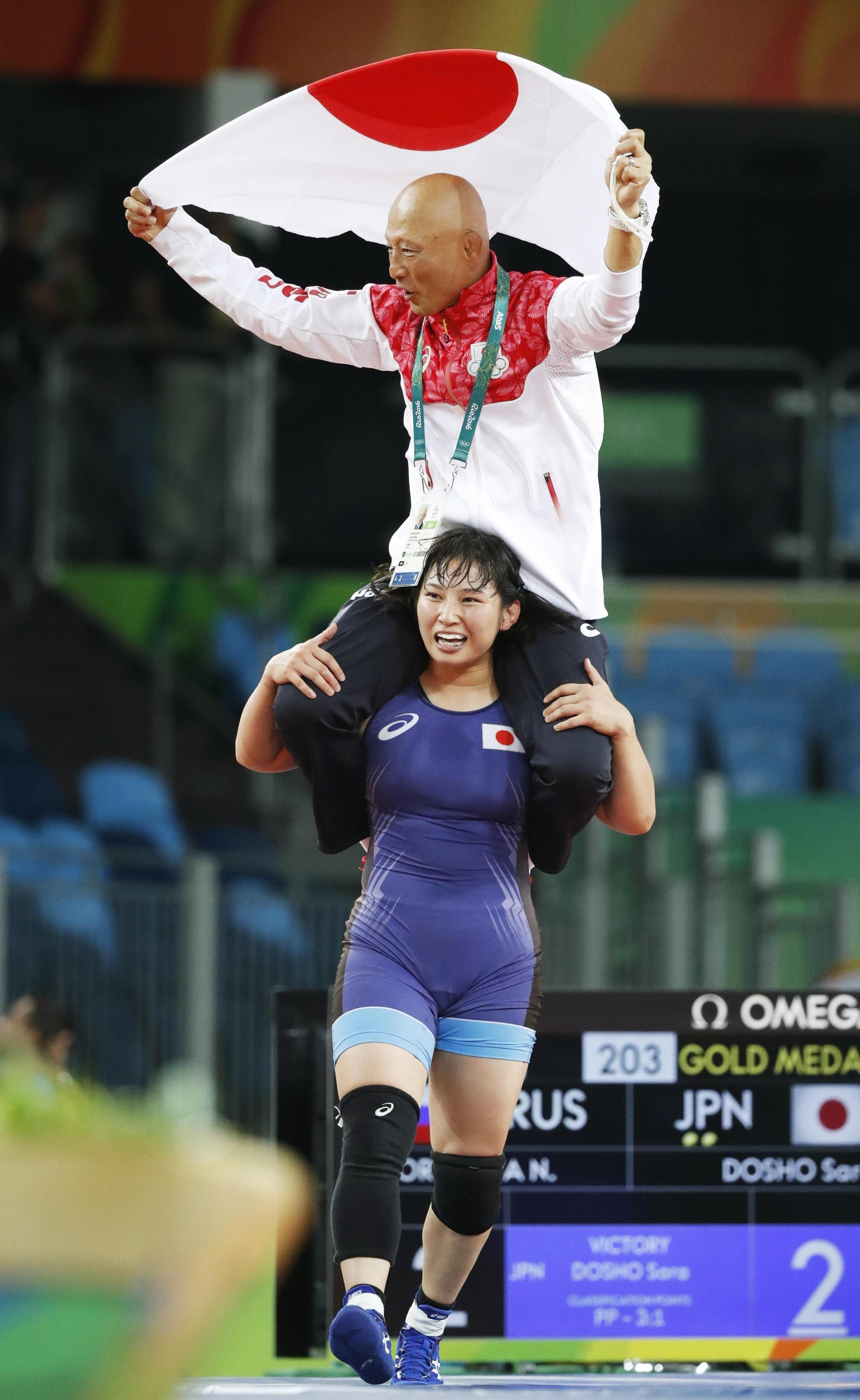 Sara Dosho celebrates with her coach Kazuhito Sakae on her shoulders after capturing the gold medal for the women's wrestling freestyle 69-kg category on Wednesday at the 2016 Rio de Janeiro Summer Olympics. | KYODO
