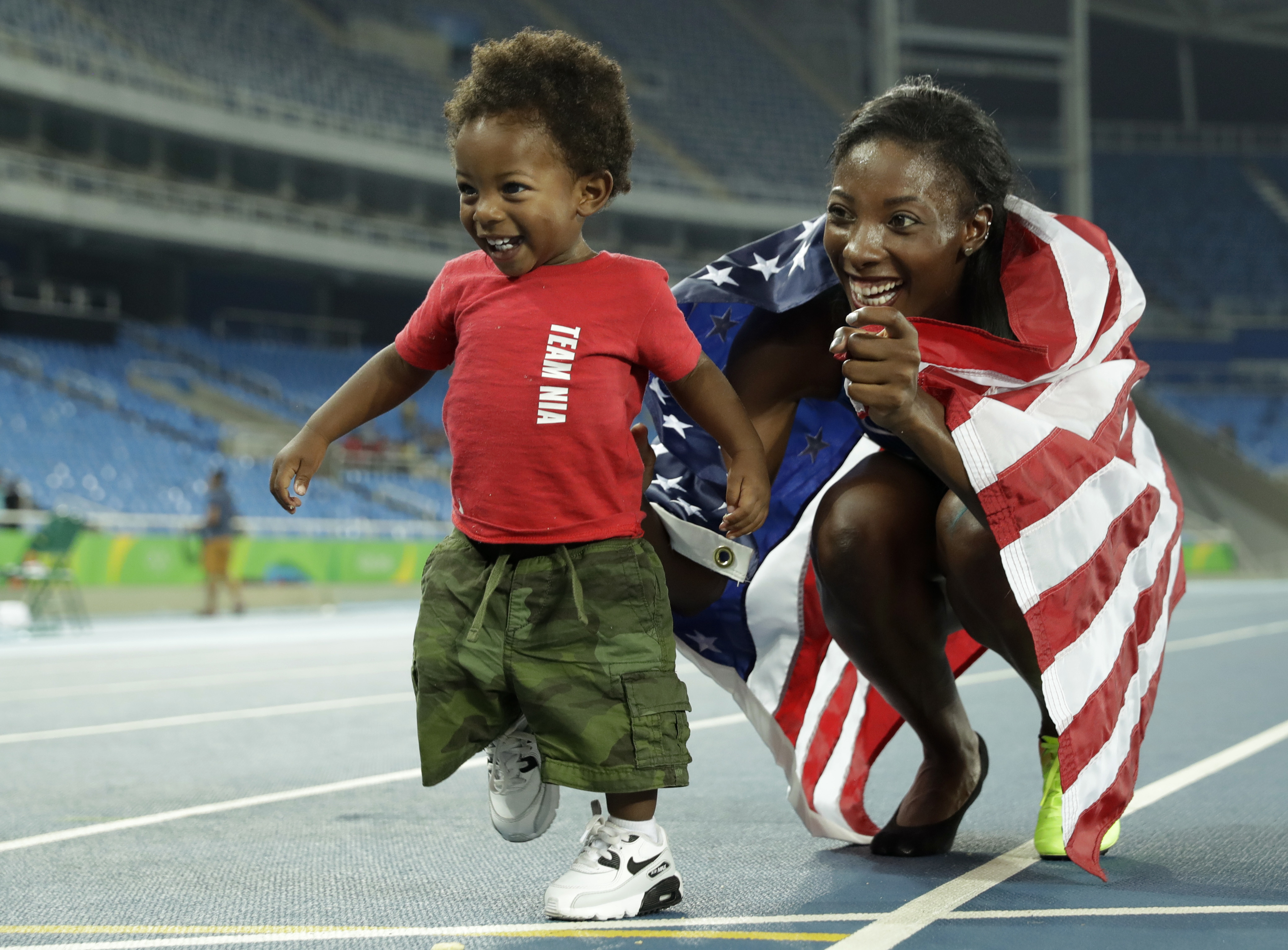 Nia Ali of the United States poses with her son, Titus, after earning the silver medal at the women's 100-meter hurdles event on Wednesday at the 2016 Rio de Janeiro Olympics. | AP