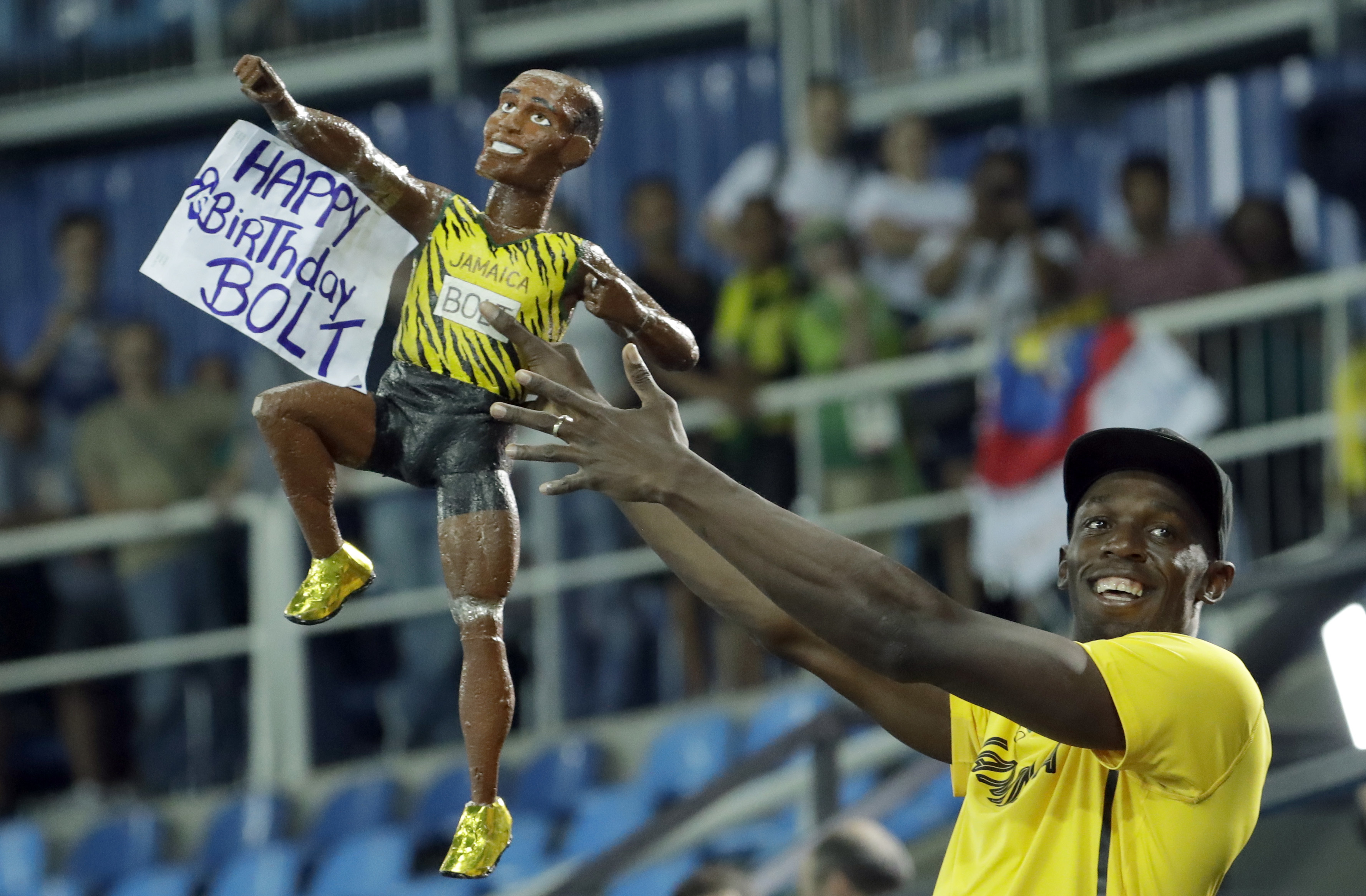 Jamaica's Usain Bolt holds a model of himself as he celebrates winning the gold medal in the men's 4x100-meter relay final at the Rio Games on Friday. He turns 30 years old on Saturday. | AP