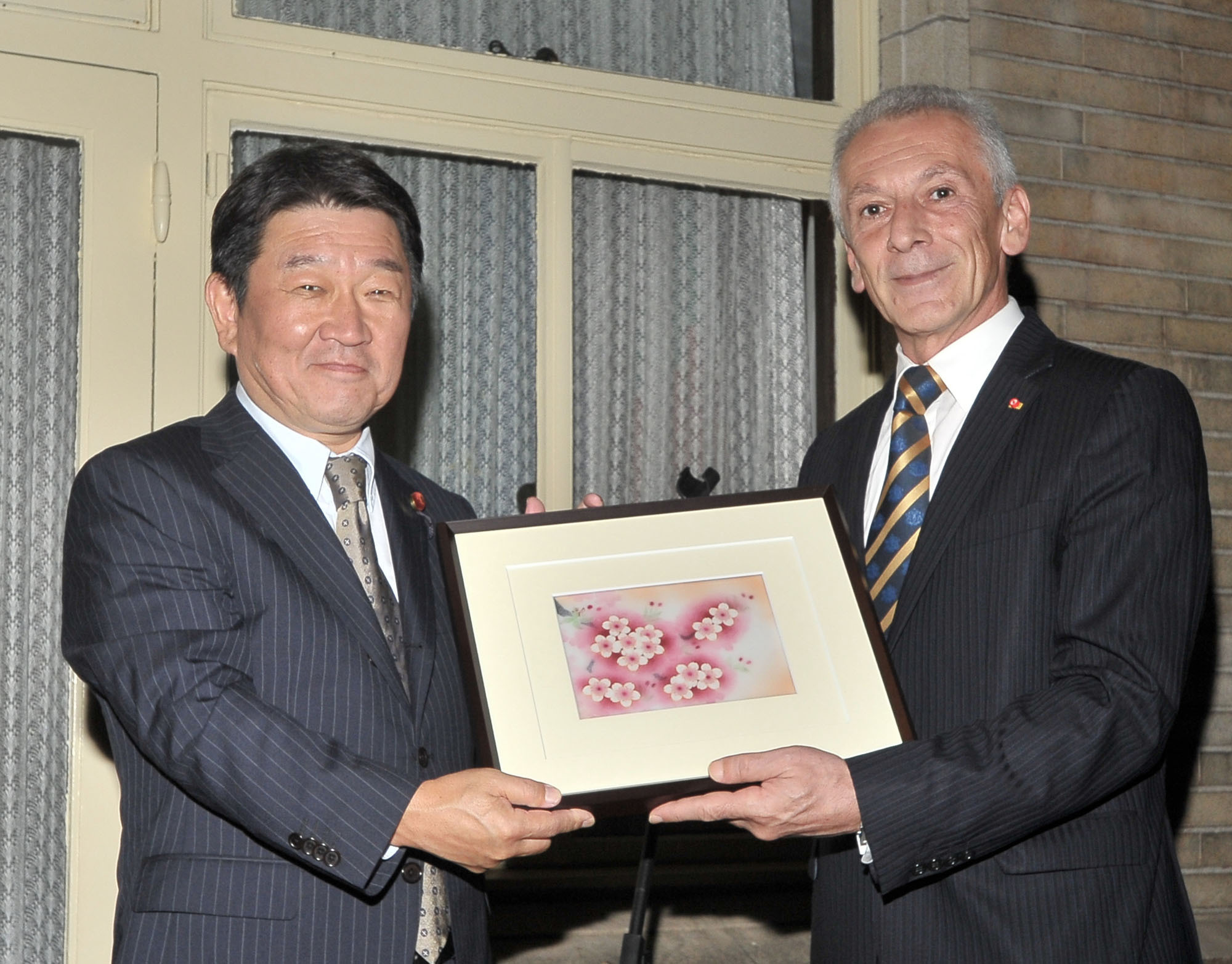 Bulgaria's Ambassador Georgi Vassilev (right) receives a sakura  print from Toshimitsu Motegi, chairman of Japan-Bulgaria Parliamentary Friendship League and Liberal Democratic Party Policy Research Council, during a farewell reception for Vassilev at the ambassador's residence in Tokyo on Sept. 29. | YOSHIAKI MIURA