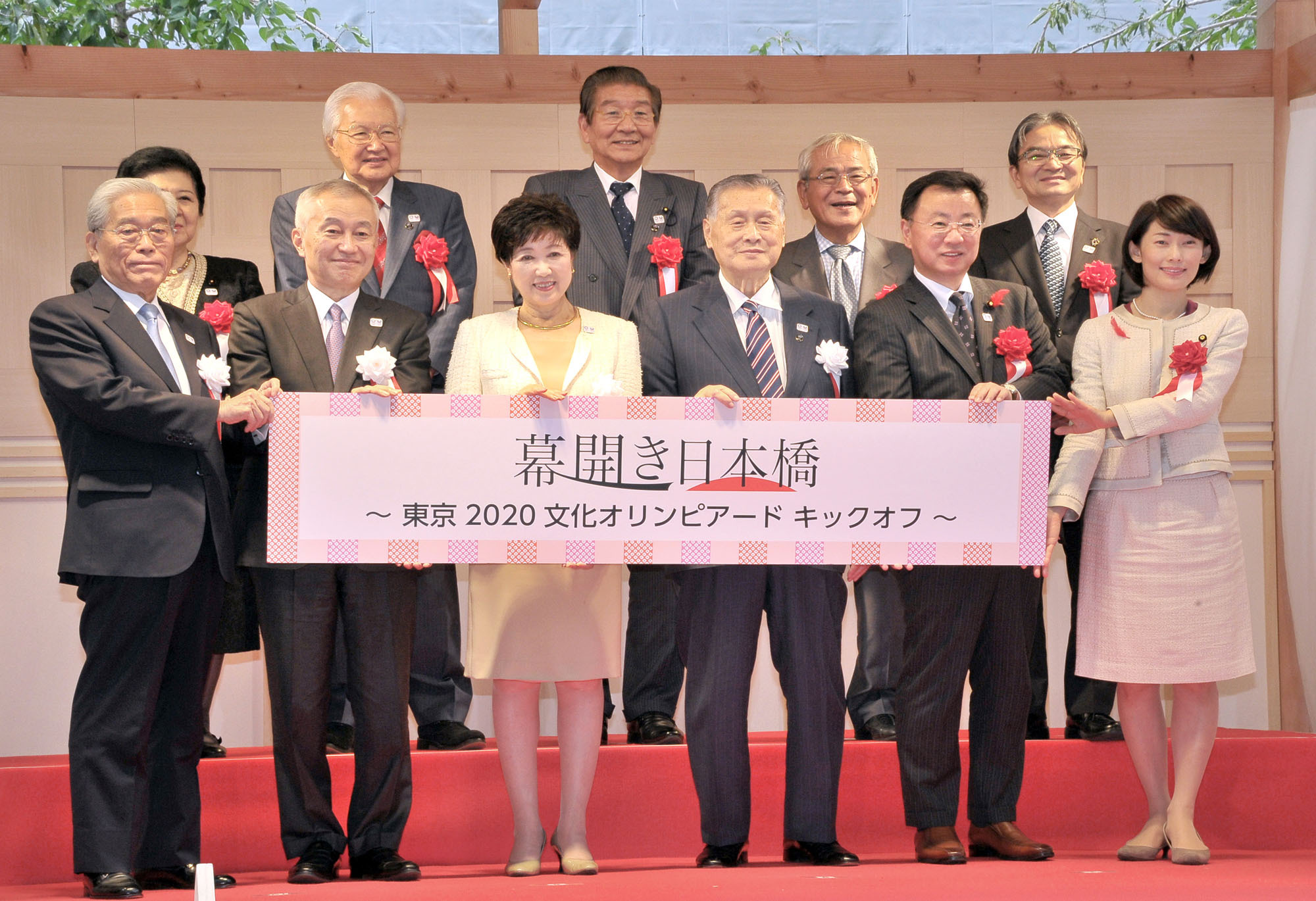 """Front row, from left: Tokyo Metropolitan Foundation for History and Culture Chair Hisashi Hieda; Mitsui Fudosan Co. President and C.E.O. Masanobu Komoda; Tokyo Gov. Yuriko Koike; Tokyo 2020 Olympic Organising Committee President Yoshiro Mori; Minister of Education, Culture, Sports, Science and Technology Hirokazu Matsuno; and Olympics minister Tamayo Marukawa pose with other project members at an opening event for the """"Tokyo 2020 Cultural Olympiad,"""" a four-year art and culture program leading up to the 2020 Games at """"Fukutoku no Mori'' in Nihonbashi, Tokyo on Oct. 7. 