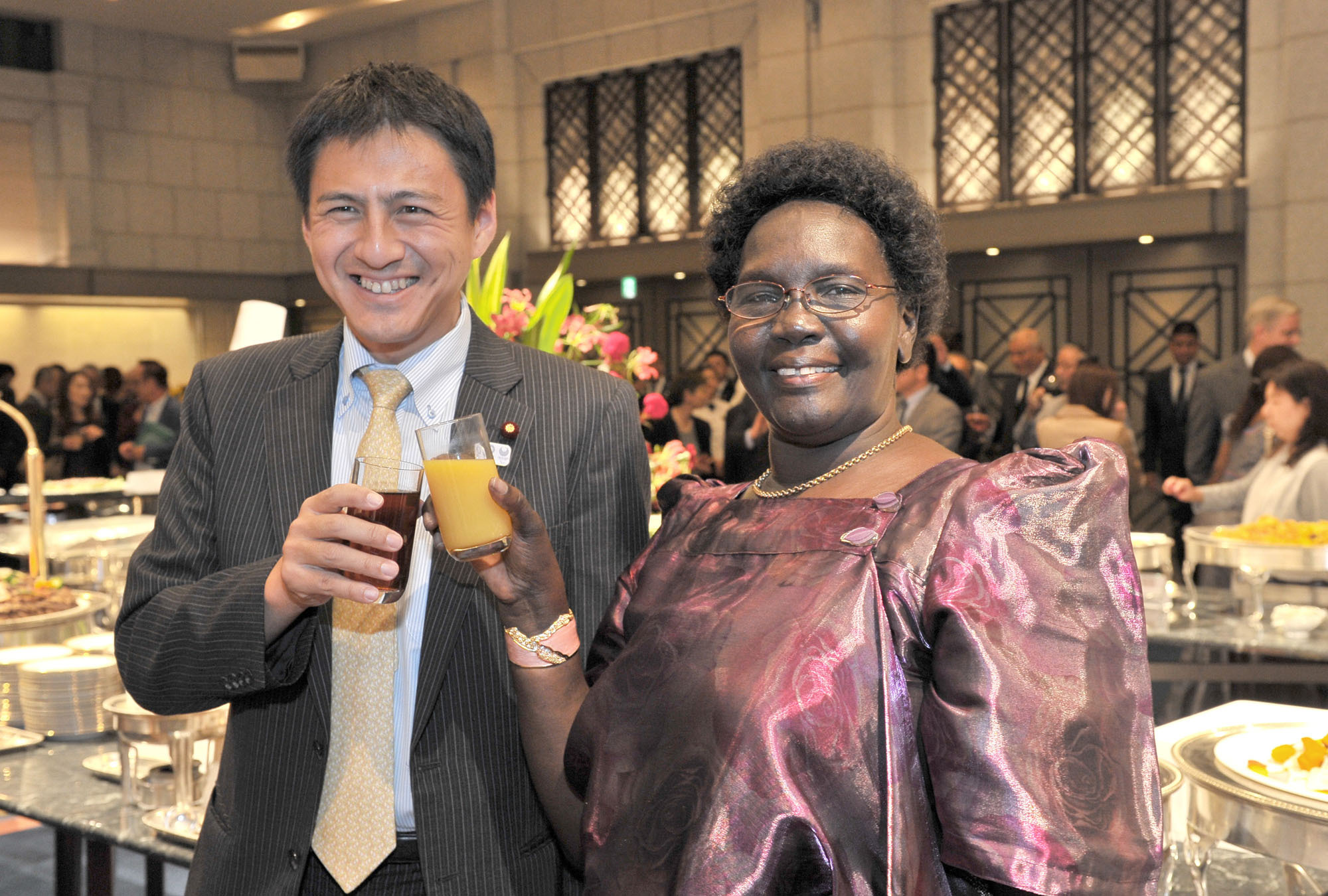 Uganda's Ambassador Betty Grace Akech-Okullo (right) shares a toast with Parliamentary Vice Minister for Foreign Affairs and House of Representatives member Shunsuke Takei at a reception to celebrate the country's 54th anniversary of independence at the Hotel Okura, Tokyo, on Oct. 9. | YOSHIAKI MIURA