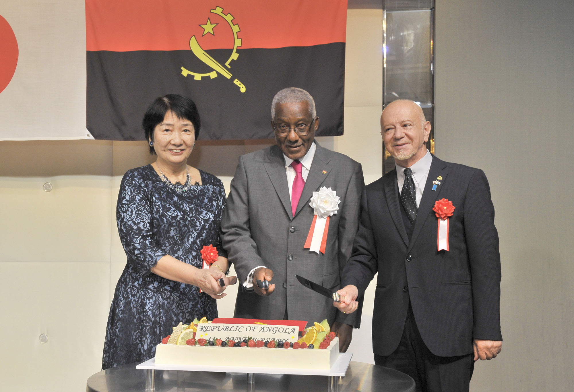 Angolan Ambassador Joao Miguel Vahekeni (center) prepares for a ceremonial cake cutting with Yumiko Akiyama (left), lead researcher of the Japan Institute of Community Social Work, and Manlio Cadelo, San Marino's ambassador and dean of the Diplomatic Corps, during a reception to celebrate of the 41st anniversary of the independence of the Republic of Angola at the Palace Hotel Tokyo on Nov. 11. |  YOSHIAKI MIURA
