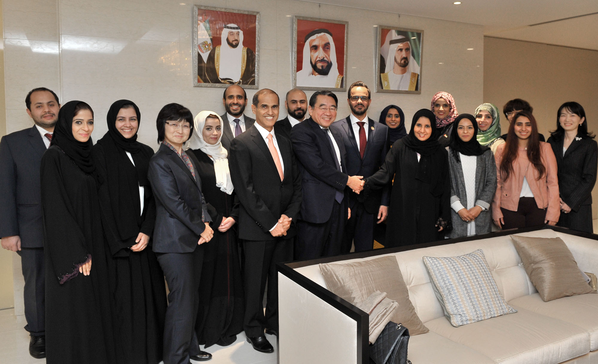 State Minister Maitha Al Shamsi (front row, fourth from right) of the United Arab Emirates shakes hands with Japan Cooperation Center, Petroleum CEO Tsuyoshi Nakai in front of UAE Ambassador Khaled Alameri at a dinner party at the ambassador's residence in Tokyo on Nov. 21. They were joined by female UAE exchange students, Japanese oil company staff and UAE diplomats. | YOSHIAKI MIURA