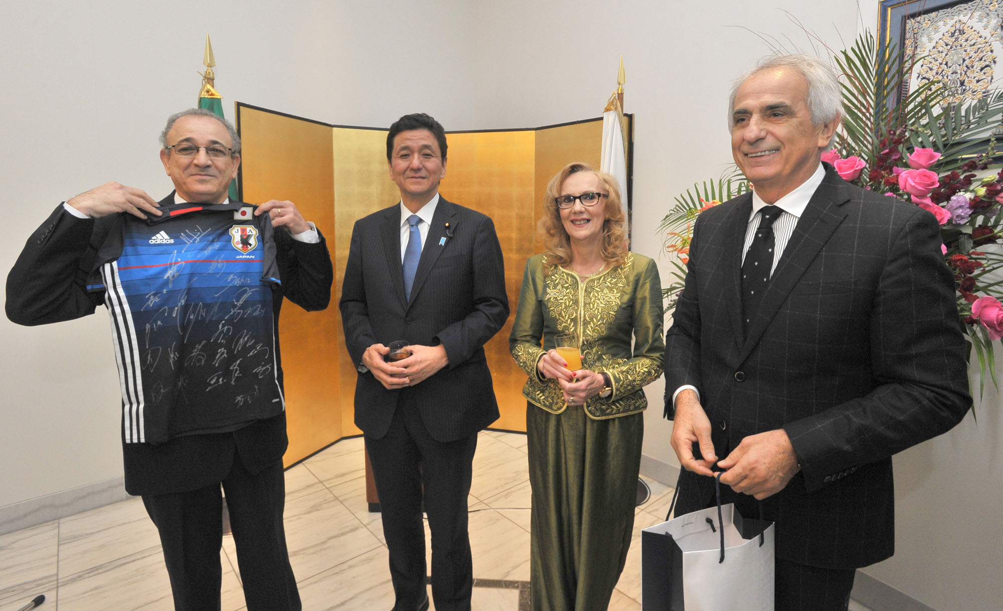 Algeria's Ambassador Mohamed El Amine Bencherif (left) holds an autographed jersey given to him by Japan National Soccer Team manager Vahid Halilhodzic (right) during a reception celebrating Algeria's 62nd national day at the embassy in Tokyo on Nov. 25. They were joined by State Minister for Foreign Affairs Nobuo Kishi (second from left) and the ambassador's wife Amira. | YOSHIAKI MIURA