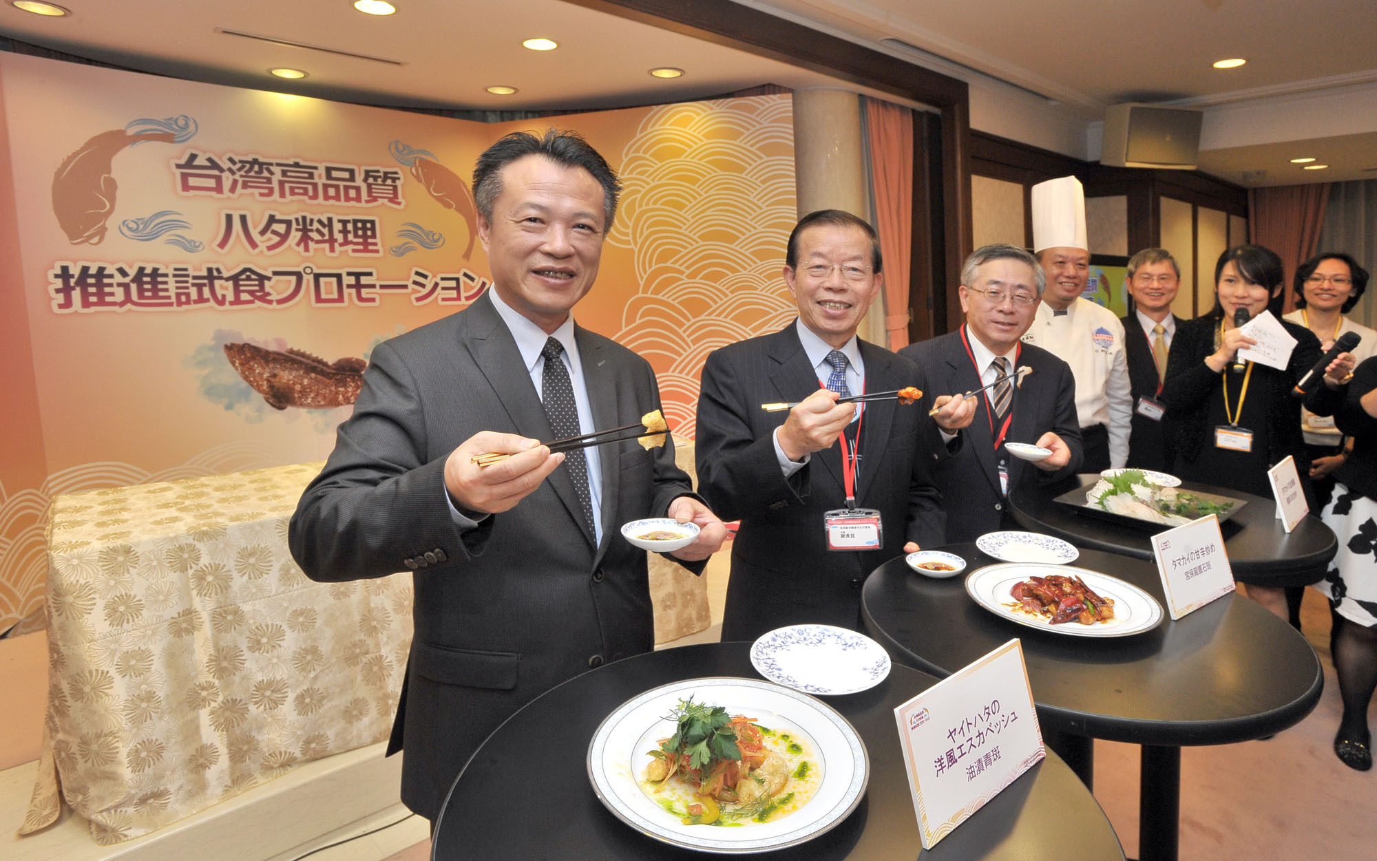 From left: Chang-Liang Weng, deputy minister of the Council of Agriculture Executive Yuan; Frank C. T. Hsieh, representative of the Taipei Economic and Cultural Representative Office in Japan; and Toshiro Shirasu, president of the Japan Fisheries Association hold up pieces of Taiwanese grouper at a promotional event at the Taipei Economic and Cultural Representative Office in Japan on Dec. 5. | YOSHIAKI MIURA