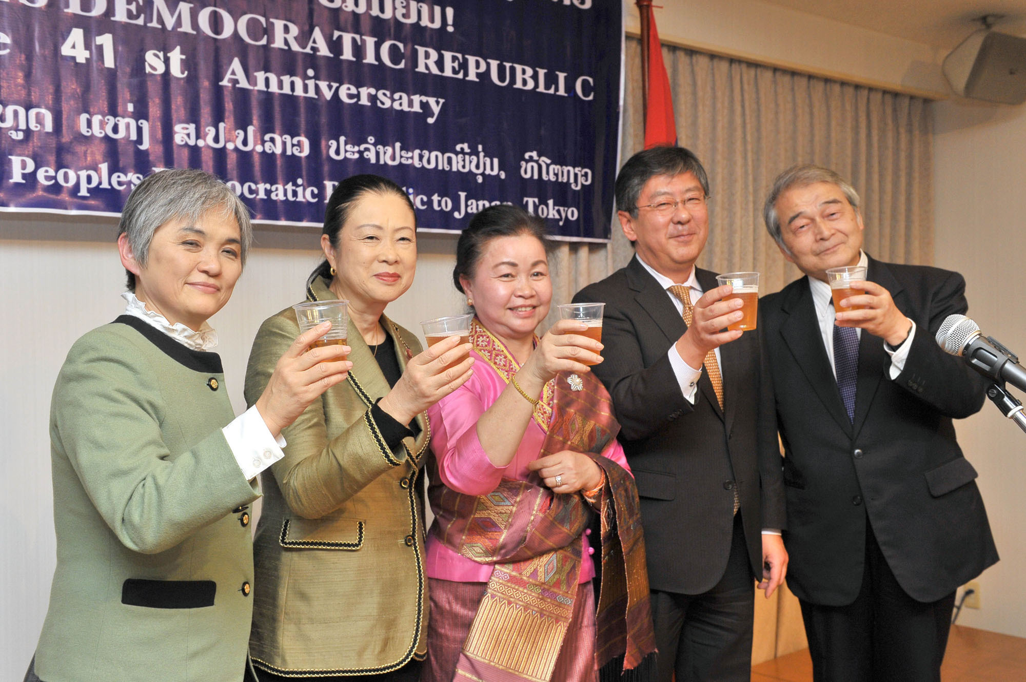 Somsanouk Vongsack (center), charge d'Affaires a.i. of Laos raises her glass with (from left) Takako Ito, assistant chief of protocol, director of the Ministry of Foreign Affairs Protocol Office; Shinako Tsuchiya, chairman of the Japan-Laos Parliamentary Friendship League; Kazuya Nashida, director general of the Ministry of Foreign Affairs Southeast and Southwest Asia Affairs Department; and Itsuo Hashimoto, Japan-Laos Association president, during a reception celebrating the 41st national day anniversary of the Lao People's Democratic Republic at the embassy in Tokyo on Dec. 4. | YOSHIAKI MIURA