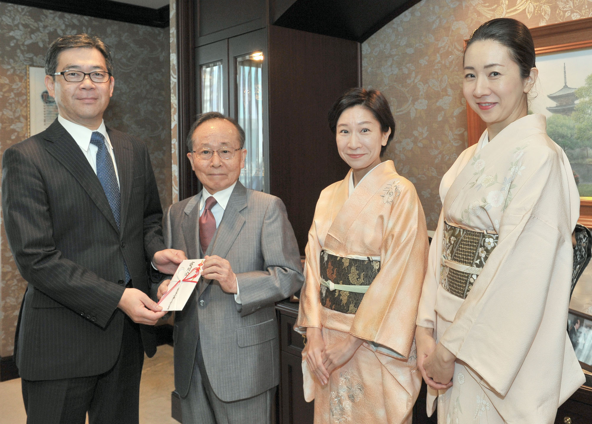 Tea ceremony school Chanoyu International Executive Director Takeya Yamasaki (second from left) presents The Japan Times President Takeharu Tsutsumi a ¥342,000 contribution for The Japan Times Readers' Fund at The Japan Times on Dec. 9. The money will be shared among overseas charities, including NPOs that help poor Cambodians and Filipinos secure better access to education. | YOSHIAKI MIURA