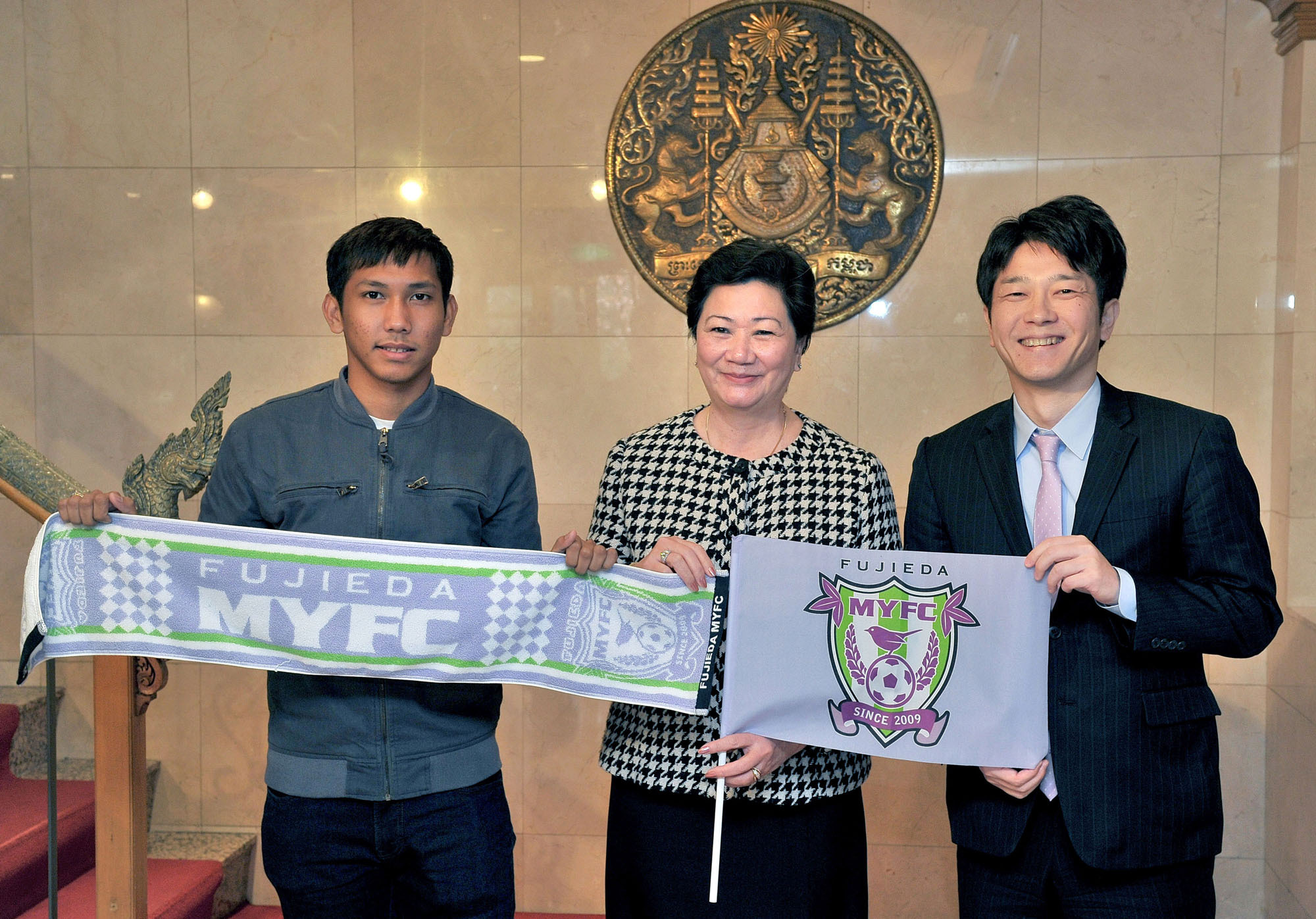 Cambodia's first J. League soccer player Chan Vathanaka (left) and Jun Koyama (right), president of Shizuoka Prefecture's Fujieda MYFC, pose during a visit with Cambodia's Ambassador Chea Kimtha at the embassy in Tokyo on Feb. 13. | YOSHIAKI MIURA