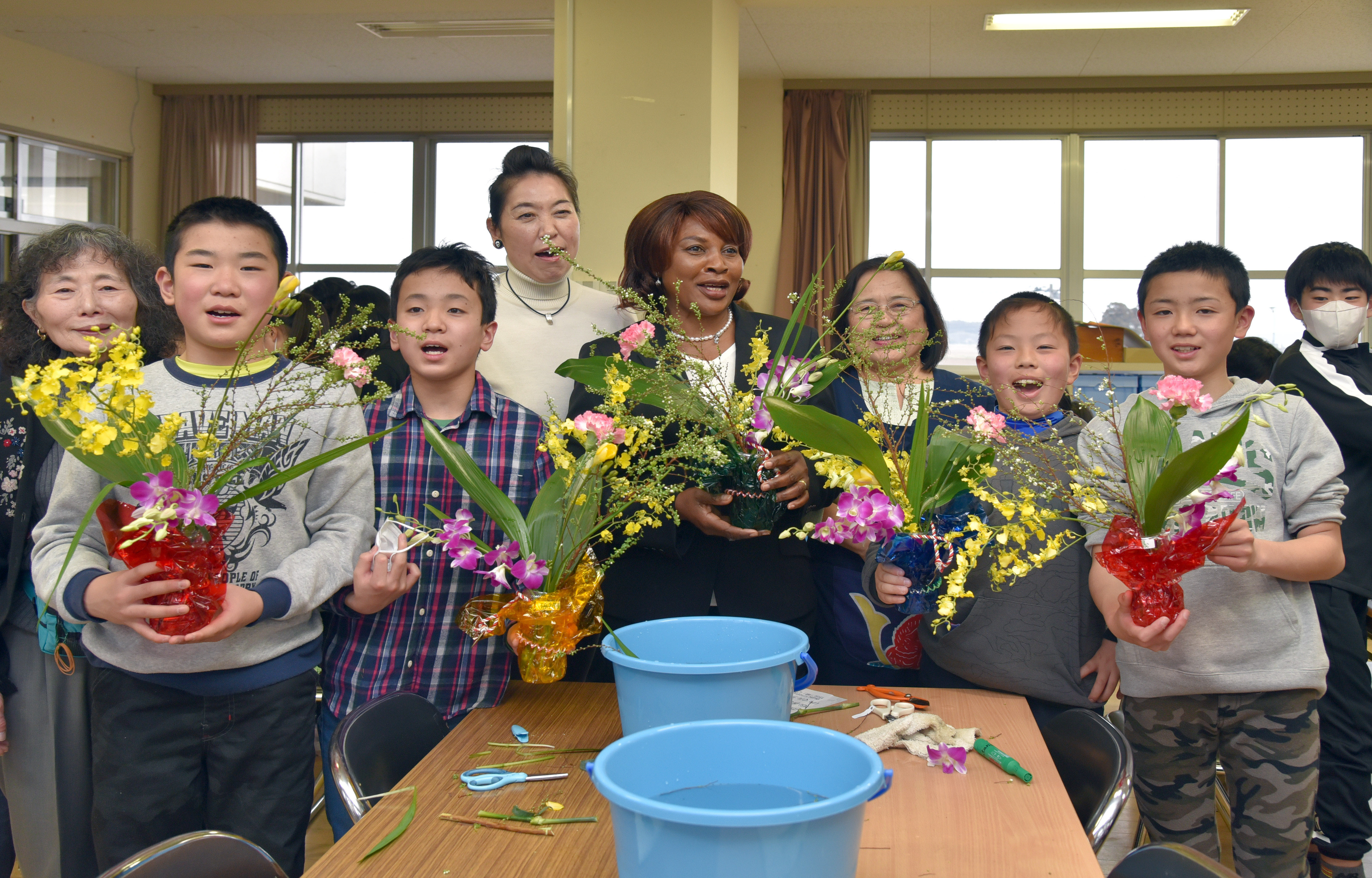 Solange P. Weya, wife of the Cote d'Ivoire ambassador (center), Ikebana International members and sixth-grade students show off their projects at an Ikebana Workshop, the fifth such workshop since the Great East Japan Earthquake and tsunami, at IItoyo Elementary School in Soma, Fukushima Prefecture, on March 2. | IKEBANA INTERNATIONAL