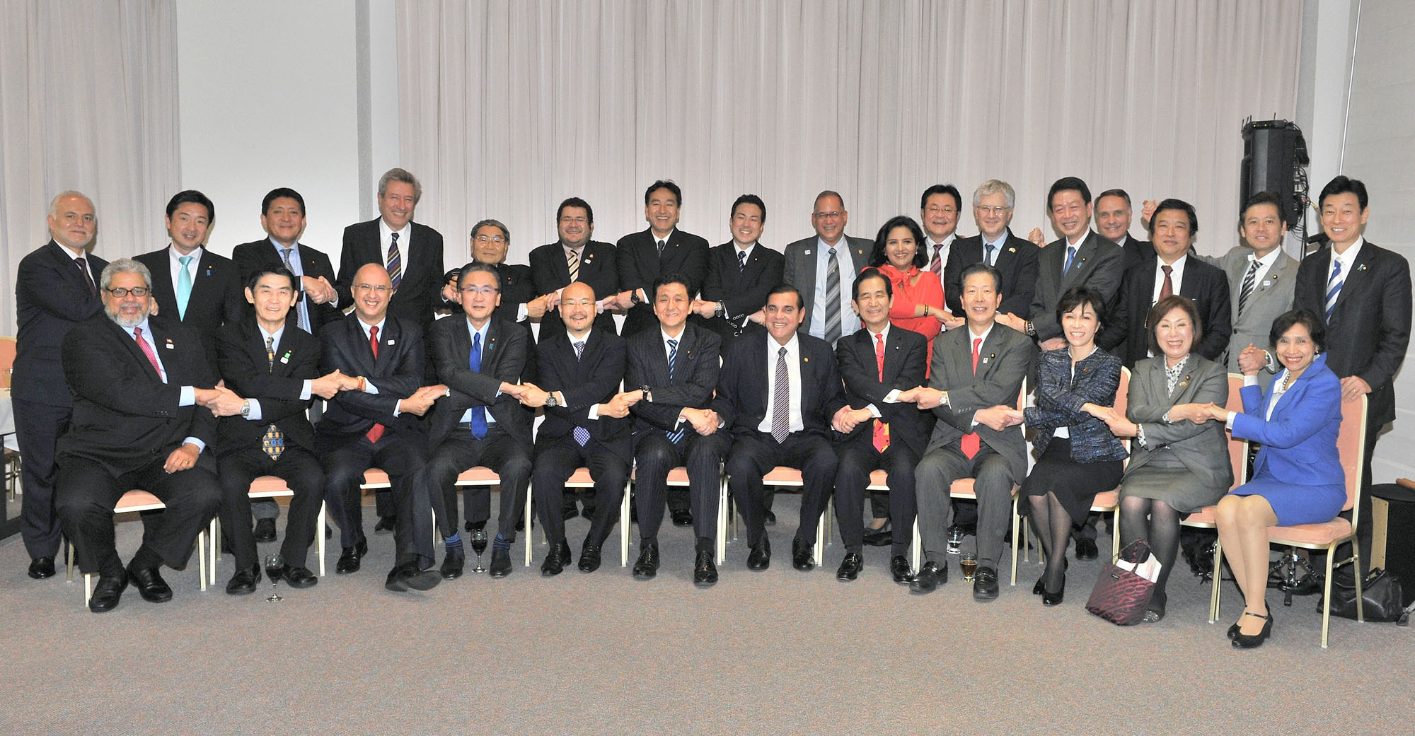 Diet members and several heads of mission of Latin American and Caribbean states, join hands during a friendly get-together at the Residence of Ambassadors in Nakameguro, Tokyo, on March 14. | YOSHIAKI MIURA
