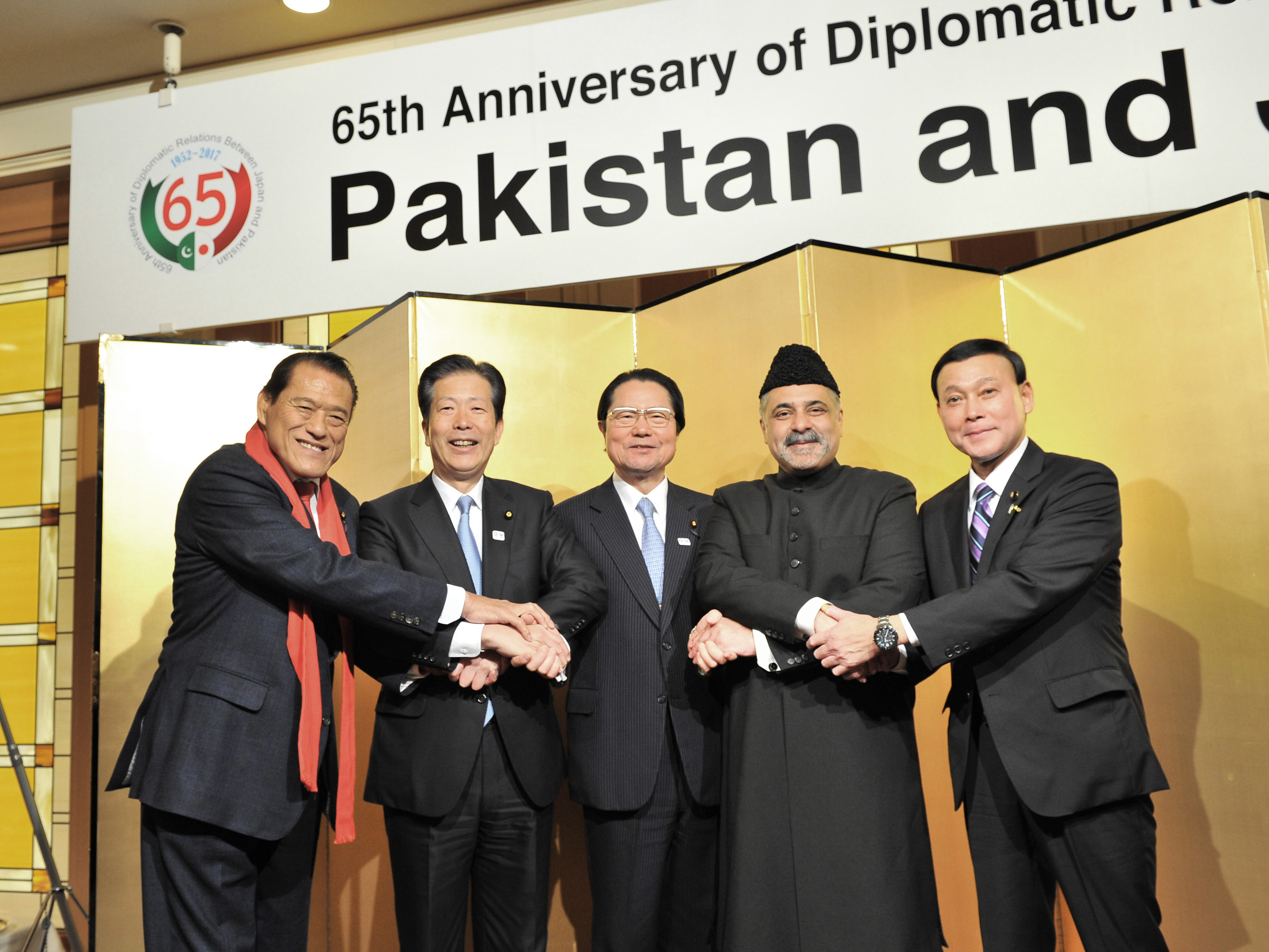 Pakistan's Ambassador Farukh Amil (second from right) joins hands with (from left) House of Councillors member Antonio Inoki,  Komeito President Natsuo Yamaguchi, Japan-Pakistan Parliamentarians' Friendship League President Seishiro Eto  and Parliamentary Vice Minister for Foreign Affairs Motome Takizawa during a reception to celebrate Pakistan national day and the 65th anniversary of diplomatic relations with Japan at the Hotel Okura, Tokyo, on March 23. |  YOSHIAKI MIURA