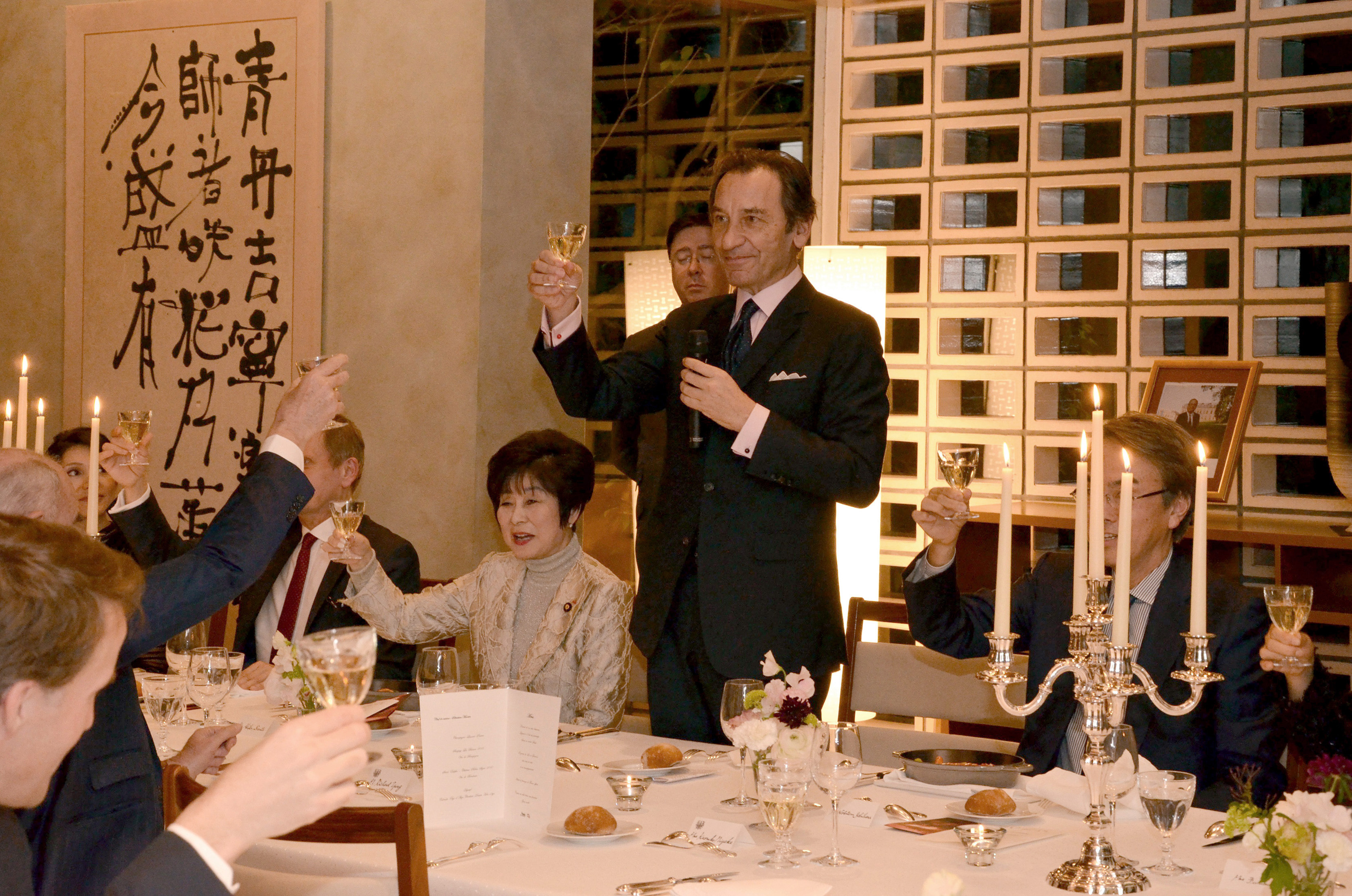 "French Ambassador Thierry Dana (center) raises a glass with President of the Japan-France House of Councillors Friendship League Akiko Santo (left), President of the House of Representatives' Friendship League Nobuteru Ishihara (right) and other guests at a ""Good France"" dinner at the ambassador's residence in Tokyo on March 17. 