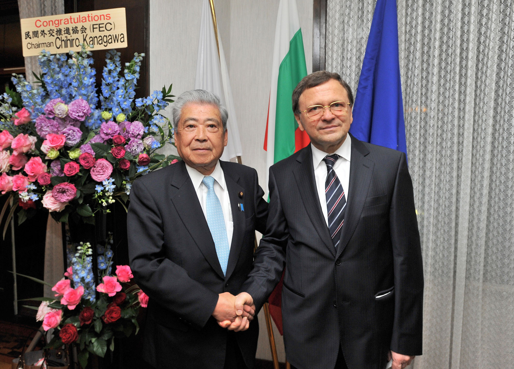 Bulgaria's Ambassador Borislav Kostov (right) shakes hands with  President of the House of Councillors and member of the Japan-Bulgaria Parliamentary Friendship League Chuichi Date during a reception to celebrate the March 3 national day of Bulgaria and cherry blossom season at the embassy in Tokyo on March 30. |  YOSHIAKI MIURA