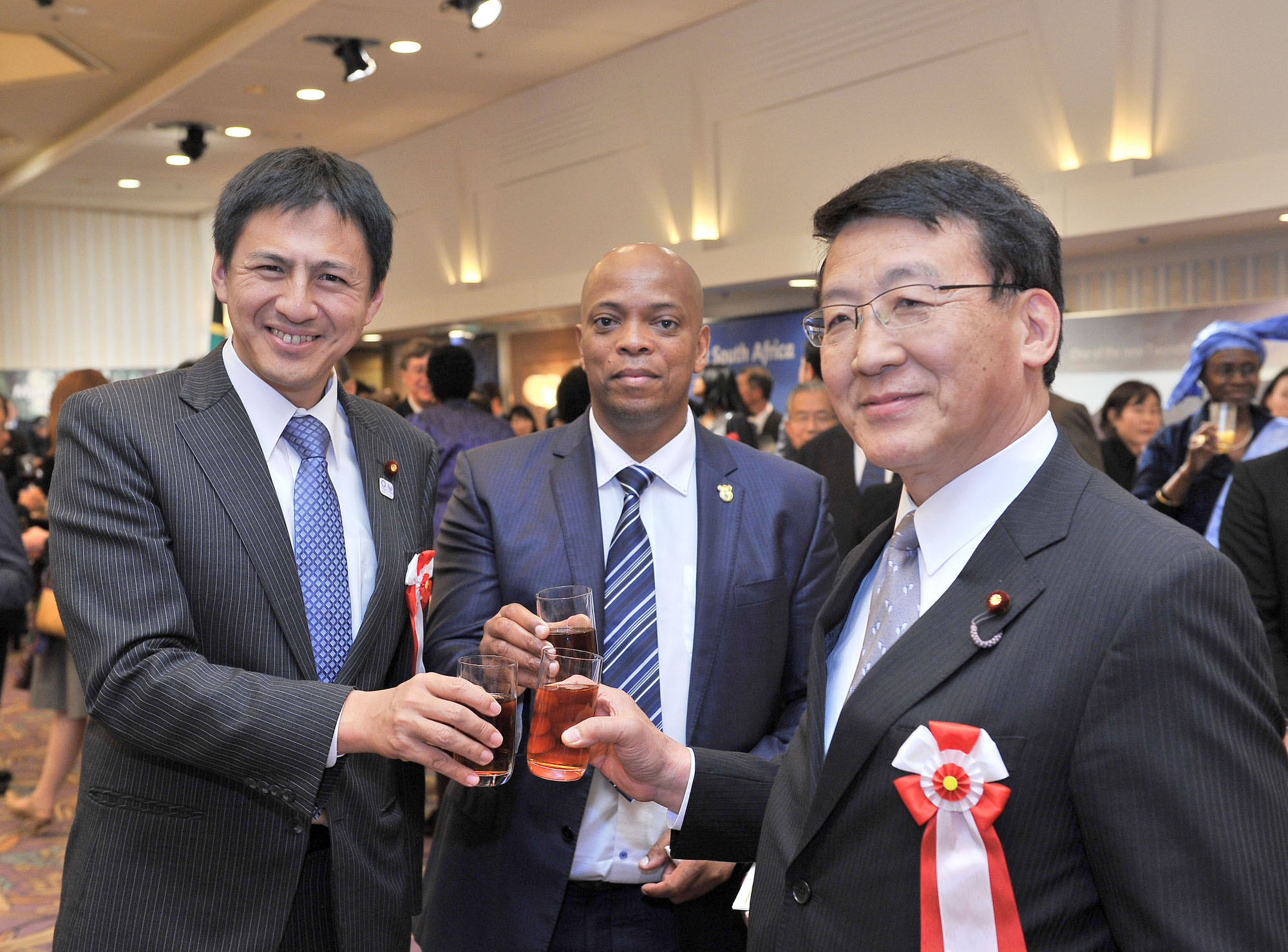 Toast masters: Royce Kuzwayo (center), charge d'affaires of the Republic of South Africa raises his glass with Shunsuke Takei (left), parliamentary vice-minister for Foreign Affairs, and Asahiko Mihara (right), acting chairperson of the Japan-African Union Parliamentary Friendship Association, during a reception celebrating South Africa's Freedom Day at Hotel Okura Tokyo on April 26. |  YOSHIAKI MIURA
