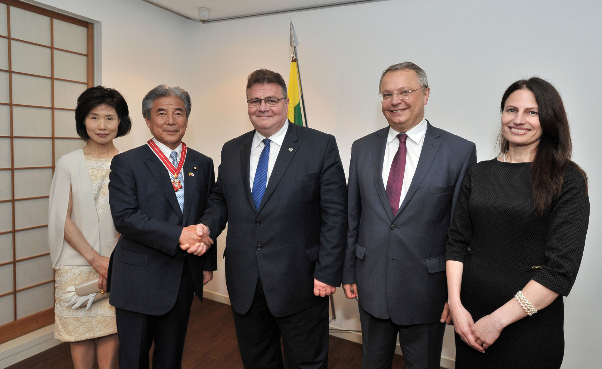 Lithuanian Foreign Minister Linas Linkevicius (center right) shakes hands with Hirofumi Nakasone, chairman of the Japan-Lithuania Parliamentary Friendship League, after receiving the Lithuanian Diplomacy Star during a reception at the embassy on May 10. Others pictured are (from left) Nakasone's wife, Mariko, Lithuanian Ambassador Egidijus Meilunas and his wife, Galina. |  YOSHIAKI MIURA