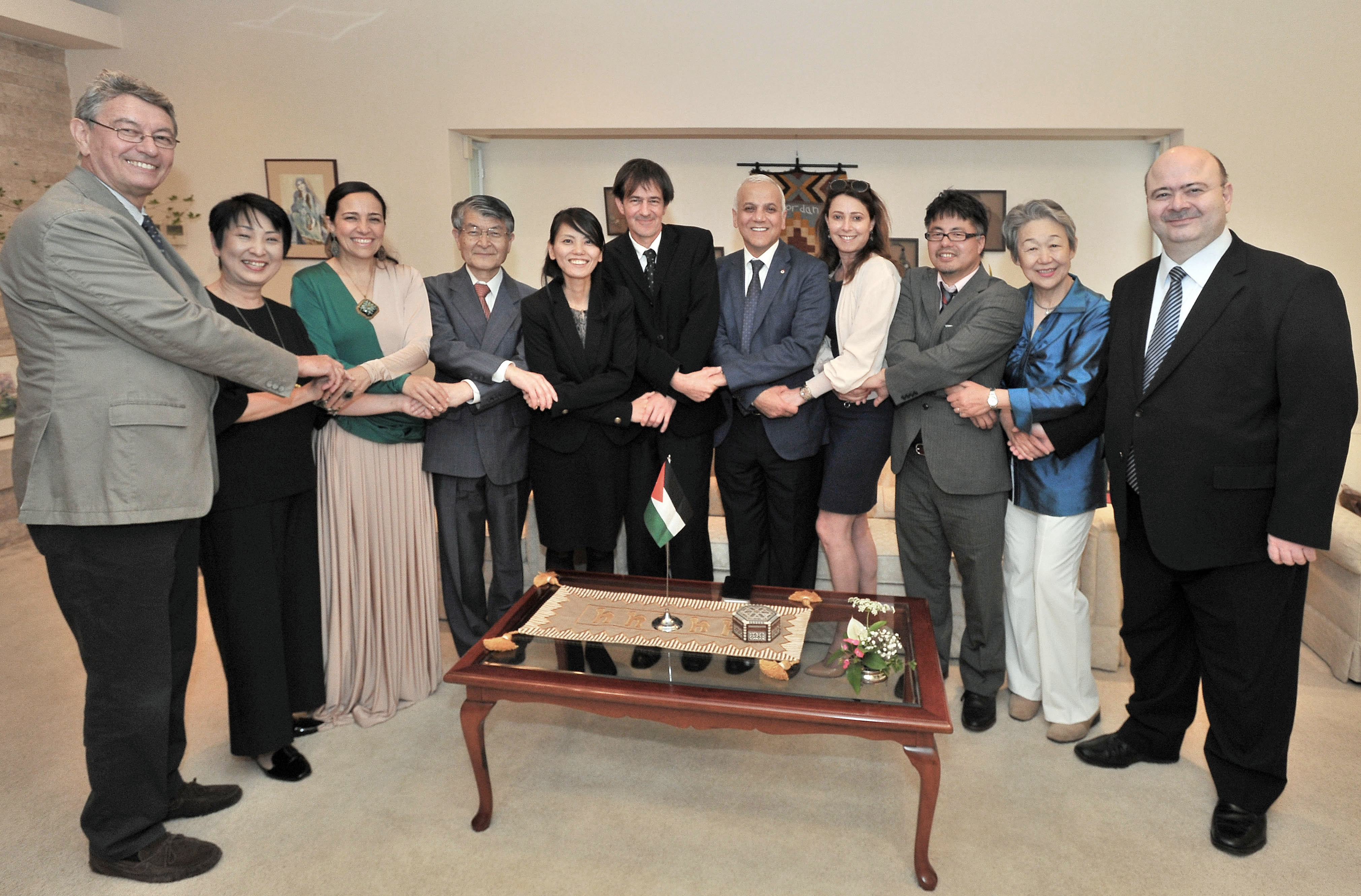 Ayman R. Al-Mufleh (center, fifth from right), secretary-general of the Jordan Hashemite Charity Organization, stands next to his wife, Loubna Bedair, at the Jordanian ambassador's residence in Tokyo on May 21 to celebrate Jordan's Independence Day with Jordan Ambassador to Japan Demiye Haddad (right) and the ambassador's wife, Shifa (third from left), as well as Japanese members of nongovernment organizations who have been supporting refugees in Jordan. | YOSHIAKI MIURA