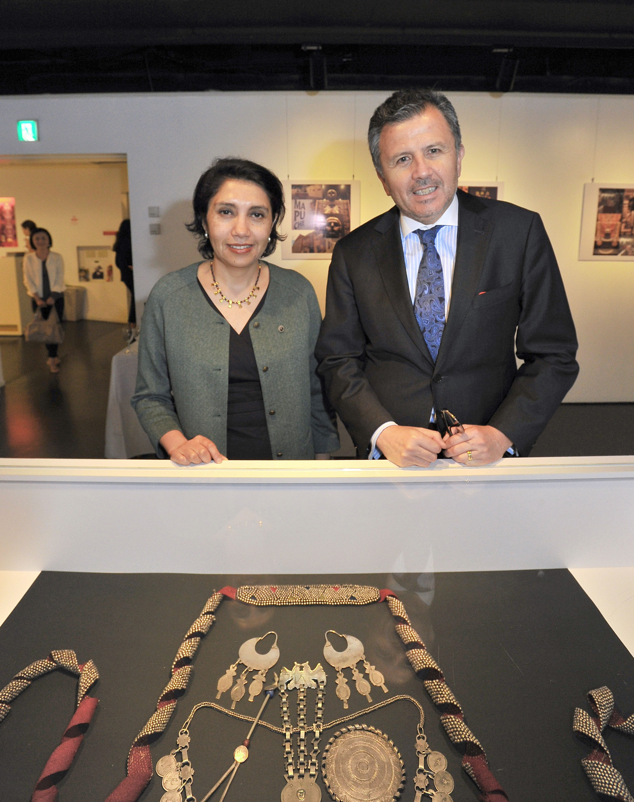 """Chilean Ambassador Gustavo Ayares (right) and Lorena Villegas, dean of Temuco Catholic University's Faculty of Arts and Humanities Chile, pose for a photo at the opening reception of an exhibition titled """"Dreams of Rutrafe: Mapuche Silver Ornaments,"""" which is on display at the Instituto Cervantes in Tokyo until July 17. 