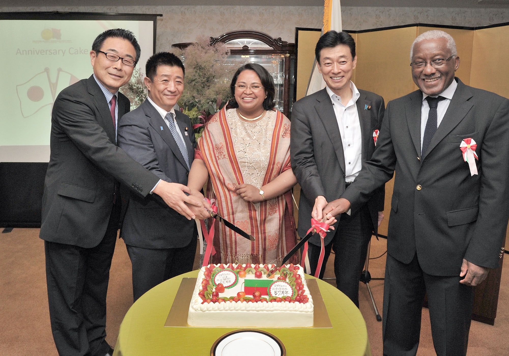 Madagascar Charge d'Affaires Rosette Rasoamanarivo (center) takes part in a cake-cutting ceremony with (from left) JICA Executive Vice President Kazuhiko Koshikawa; Takumi Ihara, parliamentary vice-minister of the economy, trade and industry; Lower House member Yasutoshi Nishimura; and Angola Ambassador Joao Miguel Vahekeni to celebrate the 57th anniversary of the independence of Madagascar and the 55th anniversary of diplomatic relations between Madagascar and Japan at the embassy in Tokyo on June 26. |  YOSHIAKI MIURA