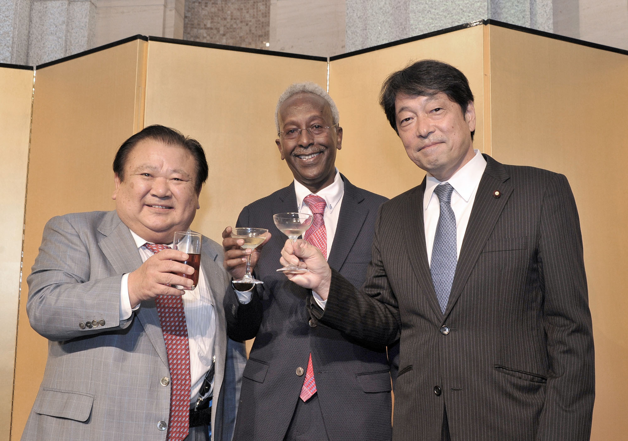 Djibouti Ambassador Ahmed Araita Ali (center) makes a toast with Kiyoshi Kimura (left), president of Sushi Zanmai, and Itsunori Onodera, former defense minister and president of the Japan-Djibouti Friendship Parliamentary Association, during a reception to celebrate the 40th anniversary of the independence of Djibouti at Hotel Okura Tokyo on June 27. |  YOSHIAKI MIURA