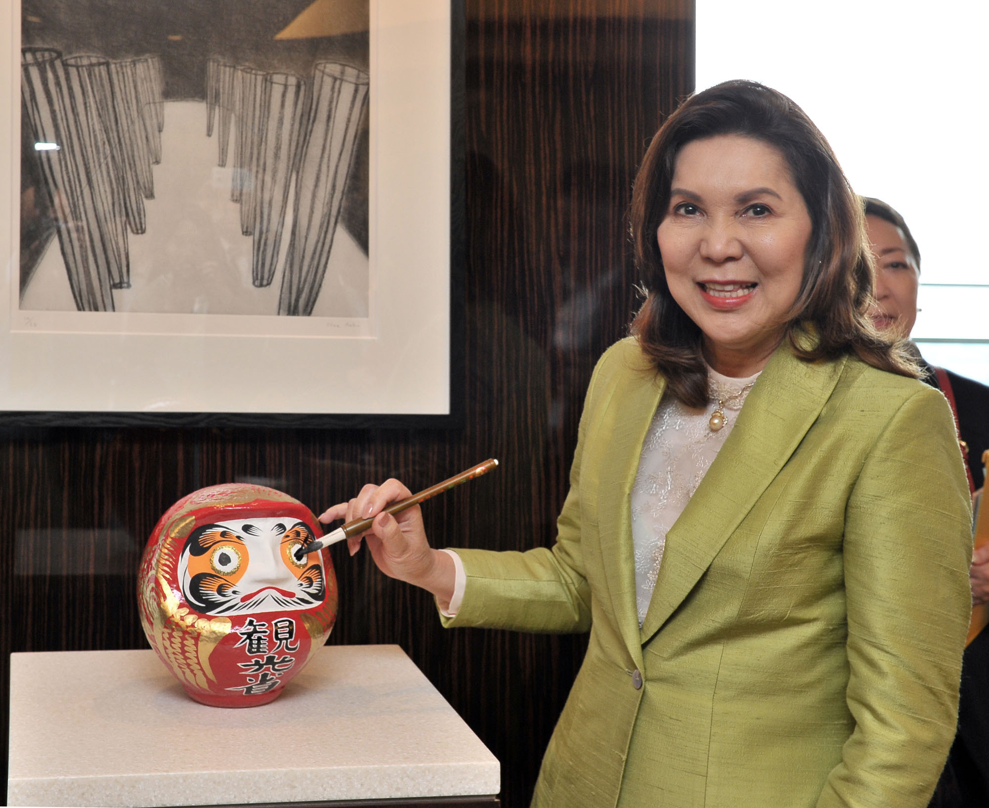 Visit to Japan Phillipine Secretary of Tourism Wanda Corazon T. Teo puts ink into the eyes of Daruma, celebrating the achievement of the goal, 500 milion sightseeing tour of Philippines from Japan, at the Palace Hotel Tokyo on June 29. | YOSHIAKI MIURA
