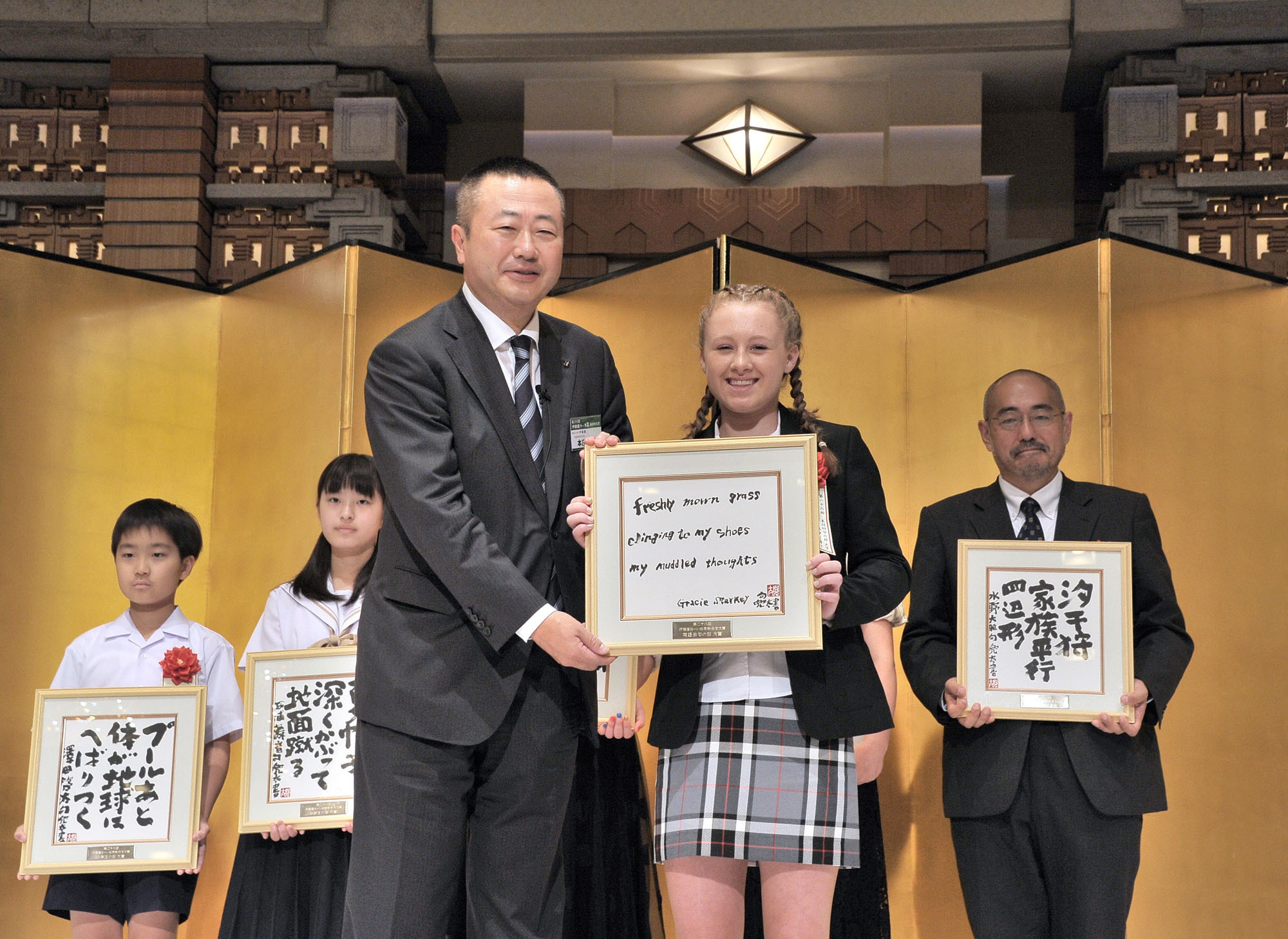 """Thirteen-year-old Briton Gracie Starkey receives a framed copy of her winning poem in the English haiku category (""""Freshly mown grass/ clinging to my shoes/ my muddled thoughts"""") from Itoen President Daisuke Honjo at the 28th Itoen Oi Ocha New Haiku Contest at Imperial Hotel Tokyo on July 6. 