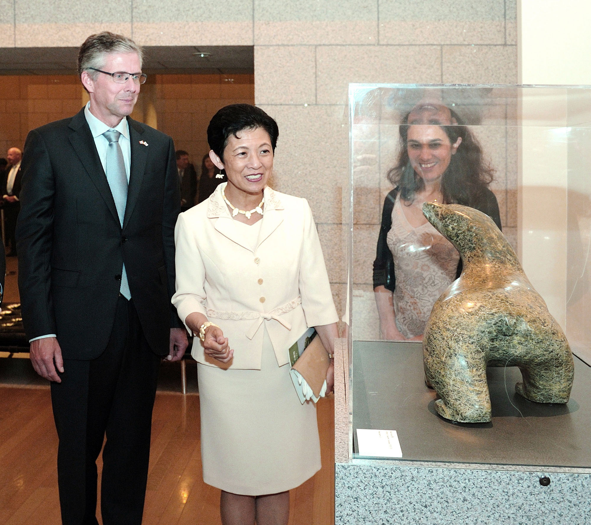 Princess Takamado (center) examines a stone Inuit carving of a bear with Canadian Ambassador Ian Burney and his wife, Sylvie Tabet, at the Canadian Embassy on Sept. 12. The exhibition runs through Nov. 21. |  YOSHIAKI MIURA