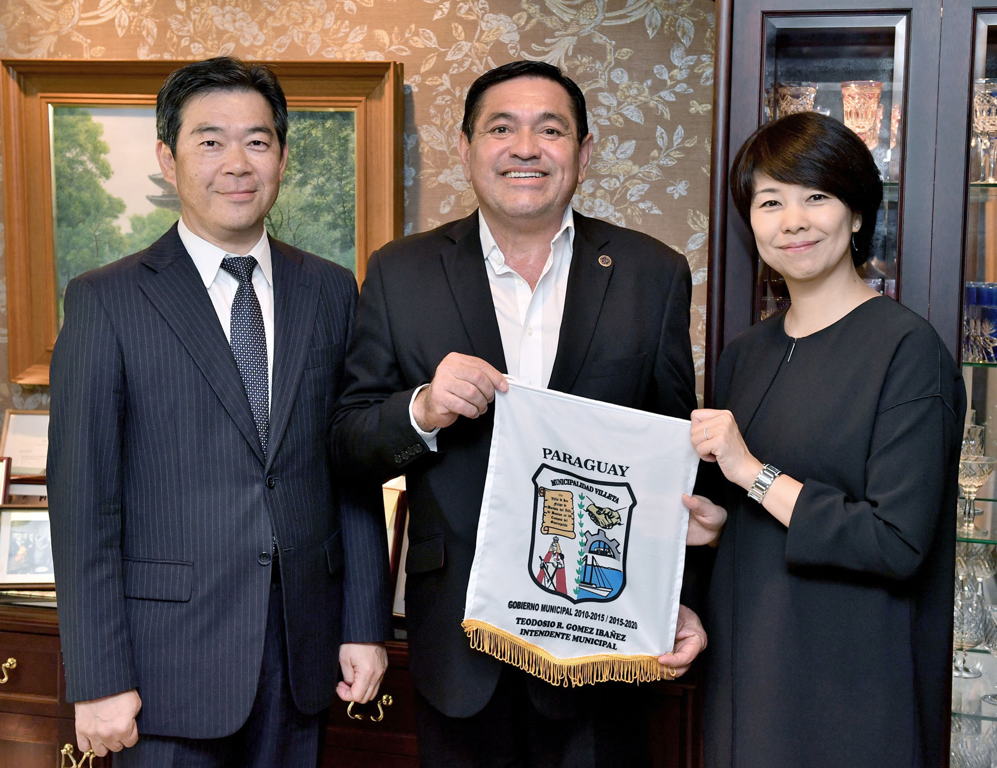 Teodosio Romilio Gomez Ibanez (center), mayor of the city of  Villeta, Paraguay,  visits The Japan Times' Tokyo office on Oct. 10, and hands a pennant bearing the city's coat of arms to Chairperson and Publisher Minako Kambara Suematsu. On the left is Japan Times President Takeharu Tsutsumi. |   YOSHIAKI MIURA