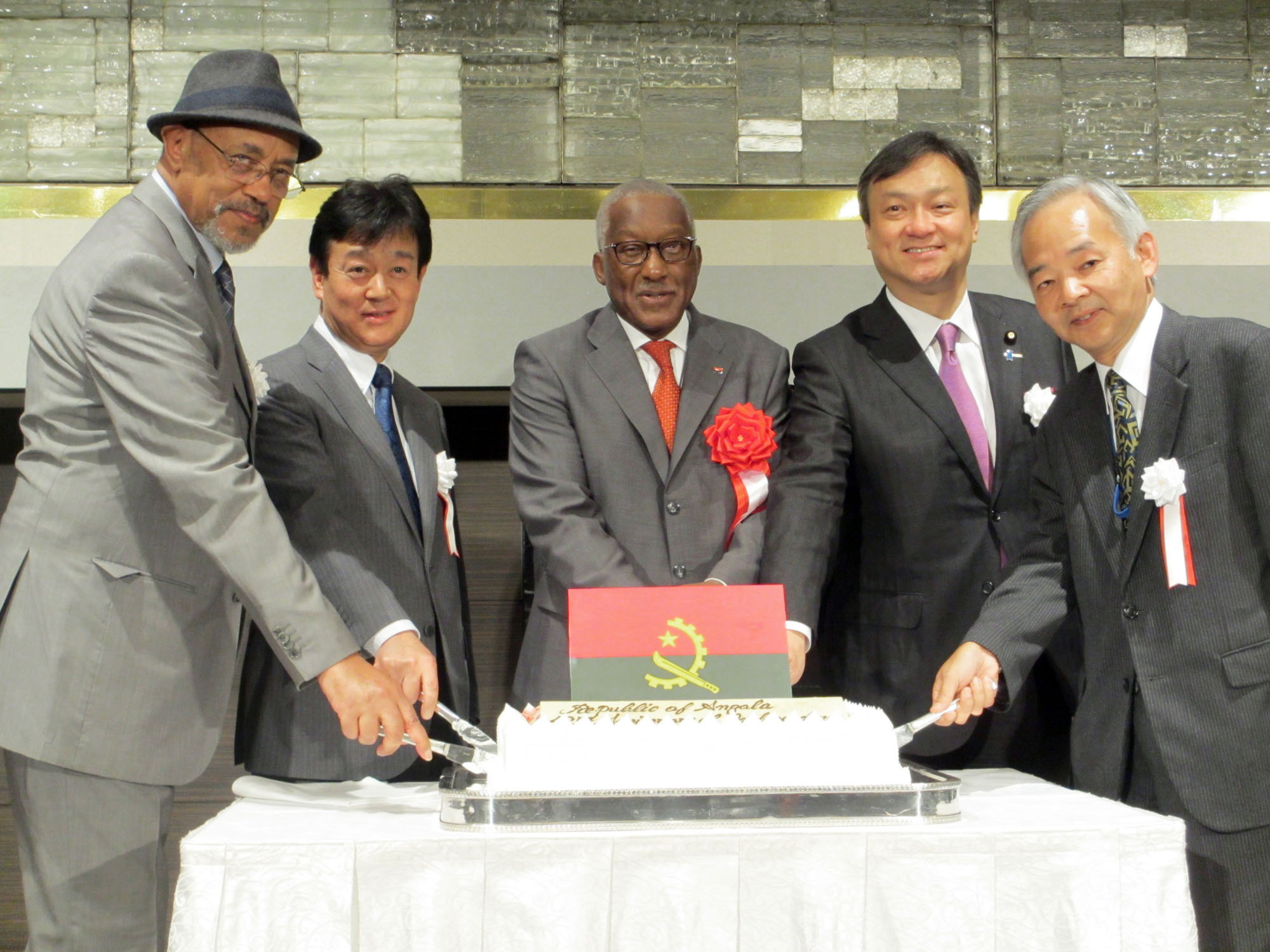 Angolan Ambassador Joao Miguel Vahekeni (center) cuts a cake  with (from left) Eritorian Ambassador Estifanos Afeworki; Takeshi Osuga, director-general of the Foreign Ministry's African Affairs Department; Iwao Horii, parliamentary vice-minister for foreign affairs; and Yoshifumi Okamura, ambassador extraordinary and plenipotentiary at the United Nations, during a reception to celebrate the anniversary of Angola's independence at Hotel New Otani on Nov. 10. |   HIROKO INOUE