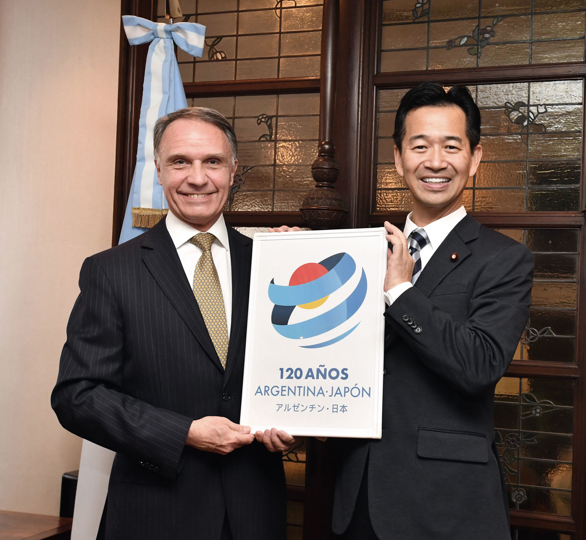 Argentinian Ambassador Alan Beraud (left) poses for a photo alongside Mitsunari Okamoto, parliamentary vice-minister for foreign affairs, during an event to celebrate the 120th anniversary of diplomatic ties between Argentina and Japan at the ambassador's official residence on Dec. 19. |  YOSHIAKI MIURA