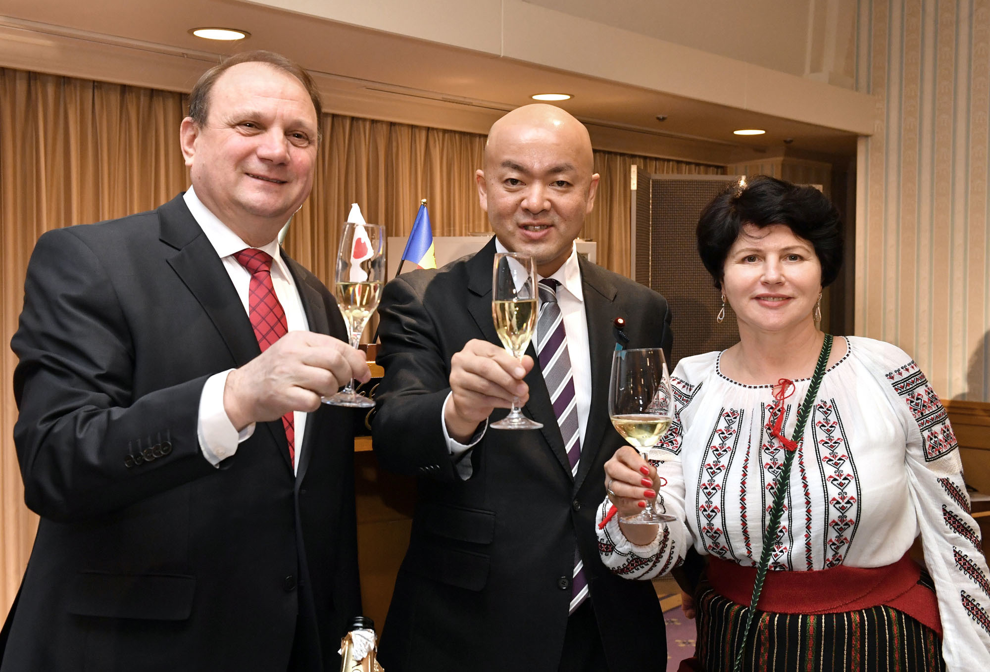 Moldovan Ambassador Vasile Bumacov (left) and his wife, Ludmila, raise their glasses during a toast with Manabu Horii, parliamentary vice-minister for foreign affairs, during a campaign to promote Moldovan wine and products such as nuts, dried fruit and honey by the Moldova Investment and Exports Promotion Organization in Japan at Hotel Okura Tokyo on Dec. 18. |  YOSHIAKI MIURA