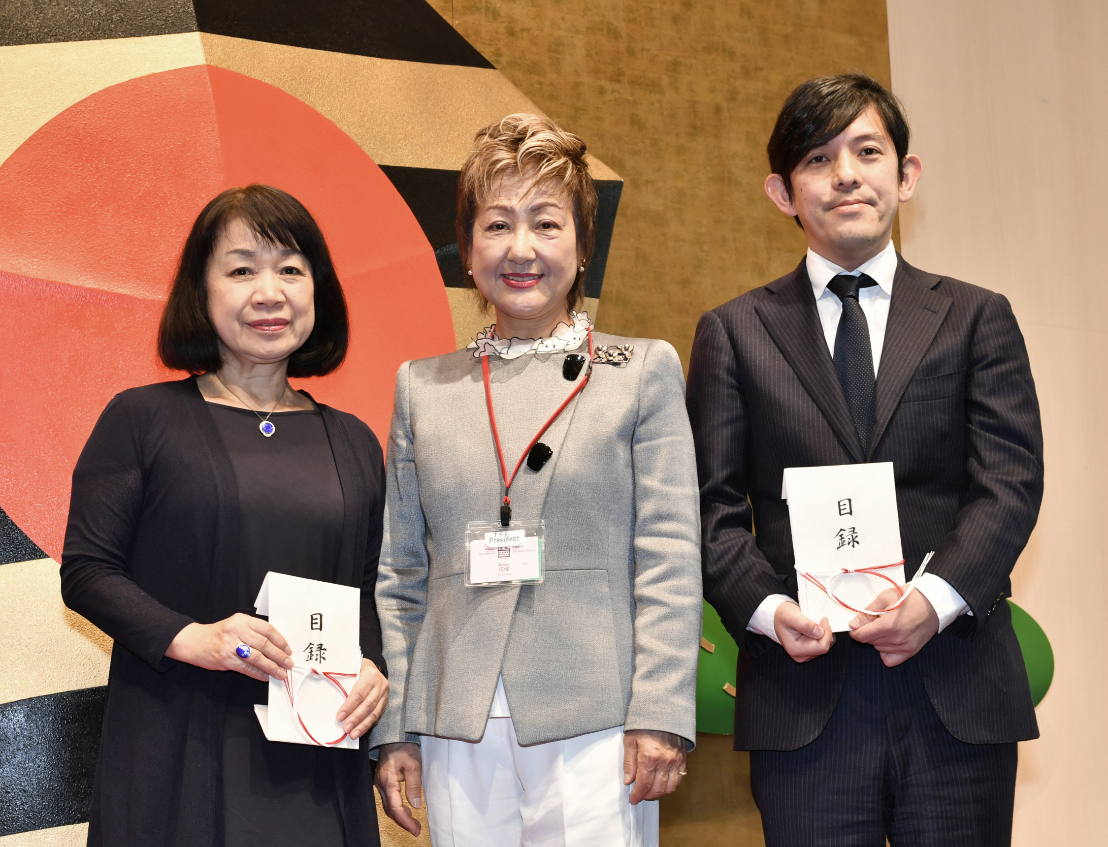 Above left: Fukuoka Gov. Hiroshi Ogawa (right) receives a donation from Belgium Ambassador Gunther Sleeuwagen on behalf of his wife, Ikebana International Fair 2017 Chairperson Rahael Zewdie Sleeuwagen, at the Ikebana International 2018 New Year Luncheon at Palace Hotel Tokyo on Jan. 18. Above right: Yusuke Numata (right), deputy sales officer and deputy general manager of The Japan Times, poses for a photo with Ikebana International Tokyo Founding Chapter President Misako Ishii (center) and Toshiko Hasegawa, acting president and secretary general of the Japan National Student Association Fund. | YOSHIAKI MIURA