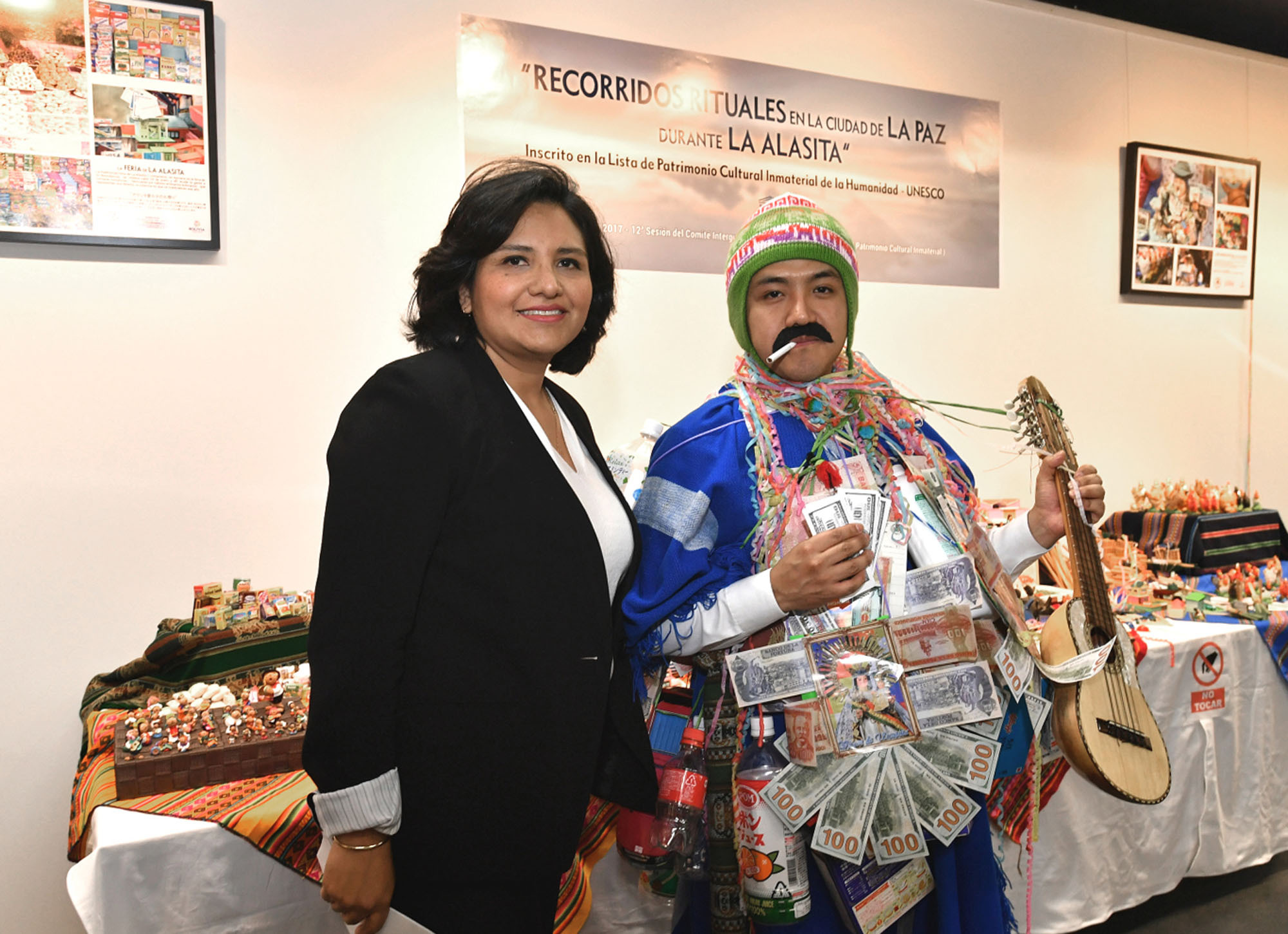 Angela Ayllon (left), charge d'affaires of Bolivia, poses for a photo next to a man dressed as El Ekeko, a god of luck and prosperity, during the opening ceremony of an exhibition being held at the Cervantes Institute to mark the nomination of the ritual journeys in La Paz during Alasita to UNESCO's Intangible Cultural Heritage list. |  YOSHIAKI MIURA