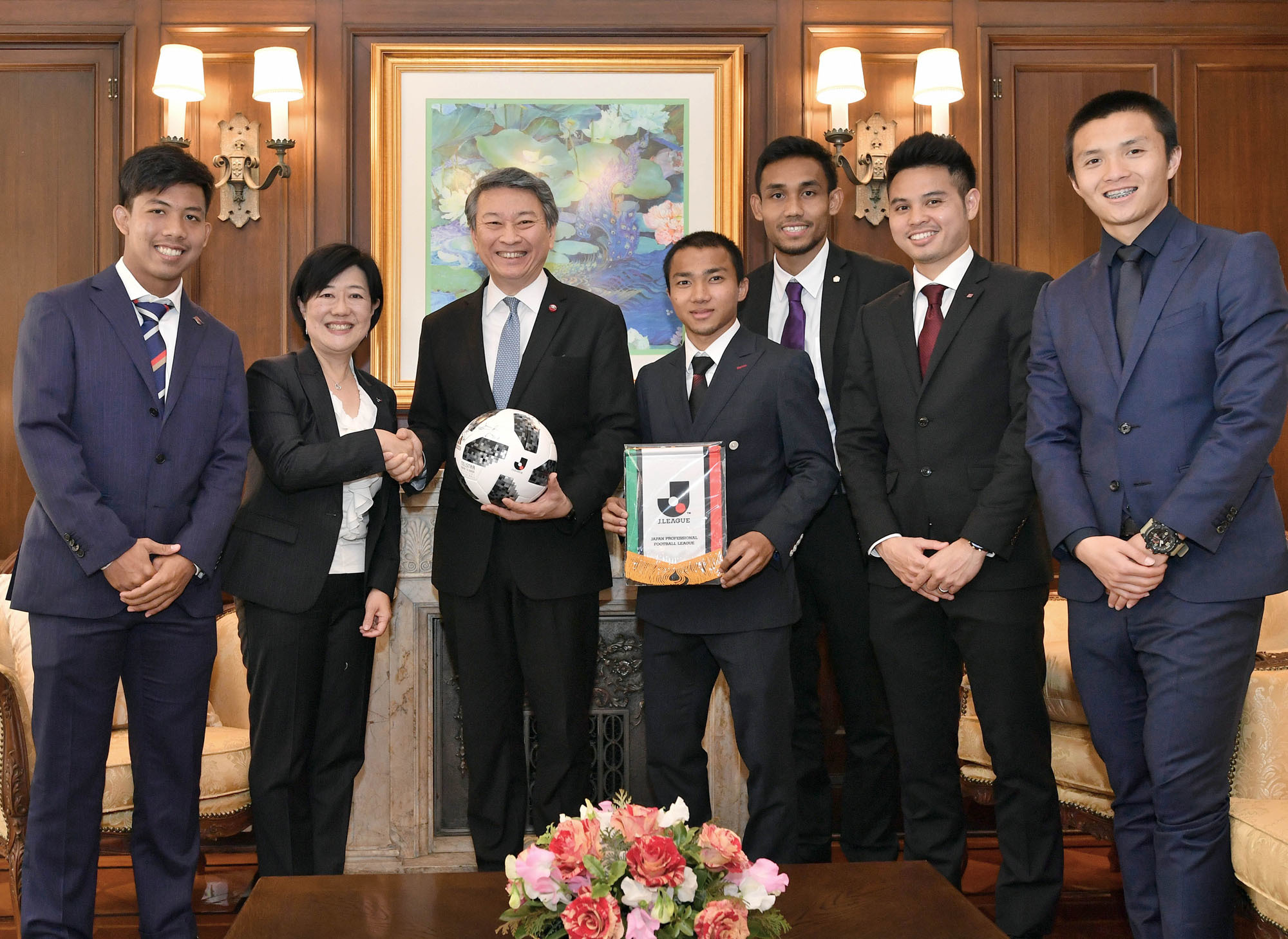 Thai soccer players in the J. League (from left) Jakkit Wachpirom (FC Tokyo), Chanathip Songkrasin (Hokkaido Consadole Sapporo ), Teerasil Dangda (Sanfrecce Hiroshima), Theerathon Bunmathan (Vissel Kobe), Chaowat Veerachart (Cerezo Osaka) and Yumiko Kinoshita (second from left), director of  the J. League's International Office, visit the Thai Embassy to present an autographed ball to Thai Ambasador Bansarn Bunnag  at the Thai ambassador's residence in Tokyo on Feb. 15. |  YOSHIAKI MIURA