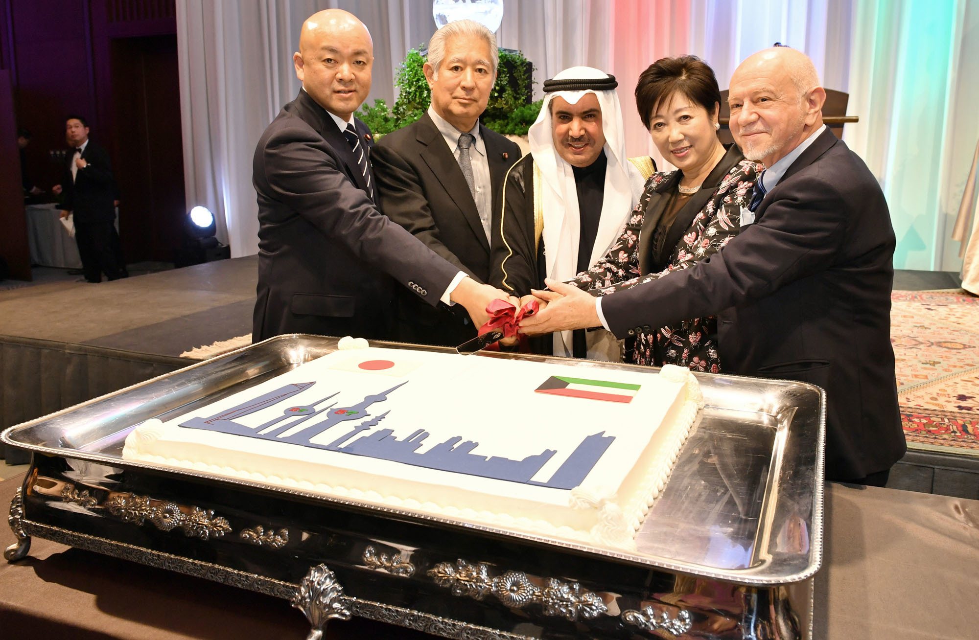 Kuwaiti Ambassador Abdul Rahman Humood Al-Otaibi (center) cuts a cake with (from left) Parliamentary Vice-Minister for Foreign Affairs Manabu Horii, Japan-Kuwait Parliamentary Friendship League Chairman Eisuke Mori, Tokyo Gov. Yuriko Koike and Manlio Cadelo, dean of the Diplomatic Corps, during a reception to celebrate the country's national day at Palace Hotel on Feb. 22. |  YOSHIAKI MIURA