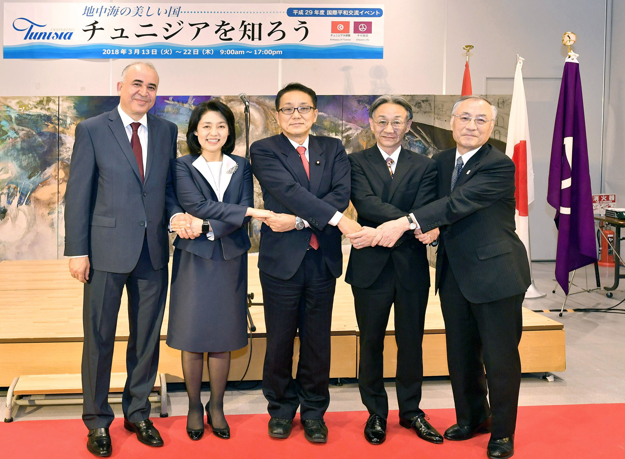 "Japanese and Tunisian artists pose for a photograph during the opening ceremony of an exhibition titled ""Inspiring Tunisia"" at Chiyoda Kumin Hall on March 12. Pictured (from left) are Tunisian Ambassador Kais Darragi; Foreign Minister Taro Kono's wife, Kaori; Kiyoshi Ejima, chairman of the Special Committee on Reconstruction after the Great East Japan Earthquake and member of the Japan-Tunisia Parliamentary Committee; artist Hideyuki Ozawa; and Chiyoda Mayor Masami Ishikawa. The exhibition is on display through March 22. 