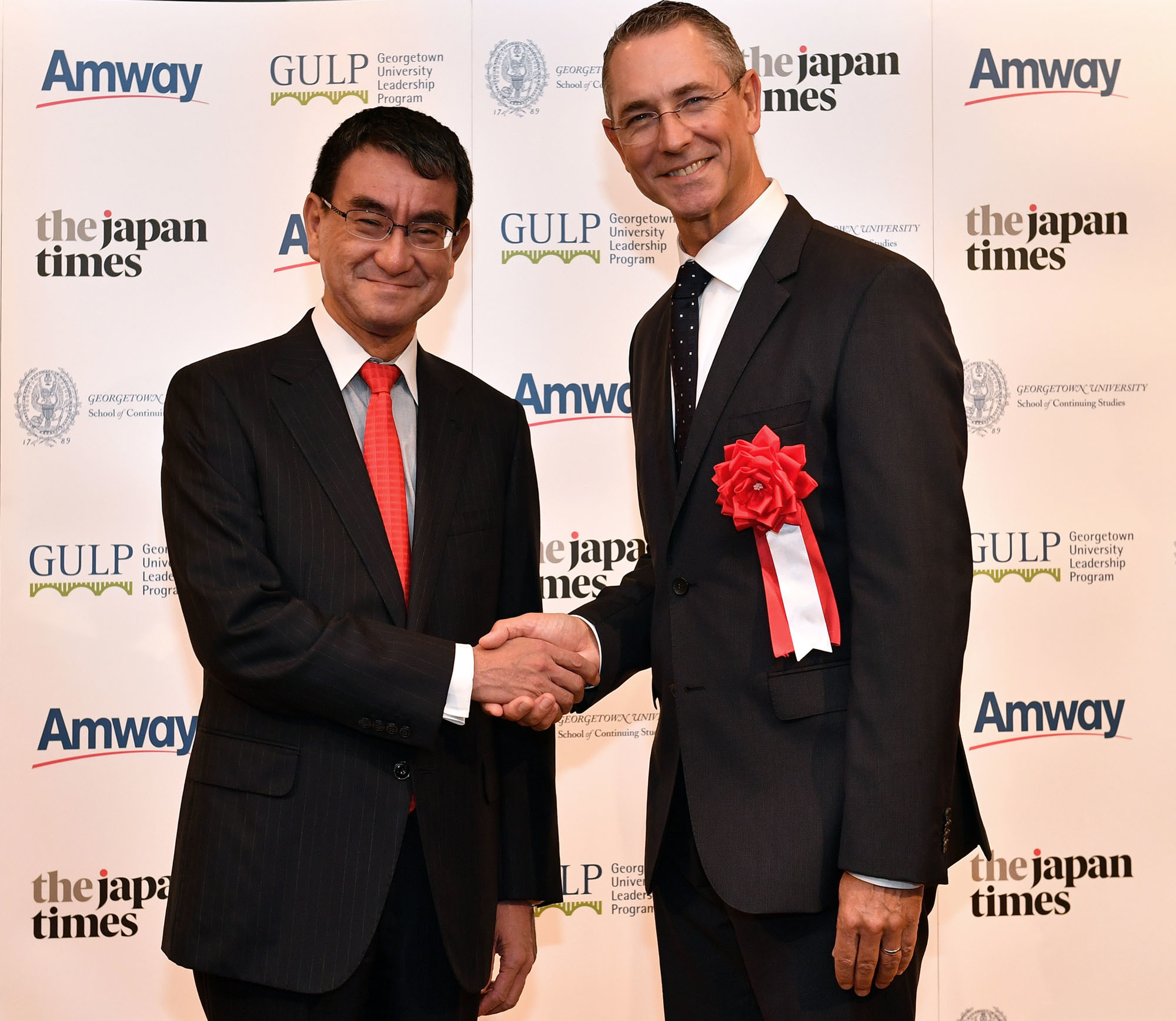 Foreign Minister Taro Kono (left) and Peter Strydom, president of Amway Japan, shake hands during a reception to celebrate the launch of the 2018 Georgetown University Leadership Program at the Cerulean Tower Tokyu Hotel in Tokyo on Sept. 10. |   YOSHIAKI MIURA