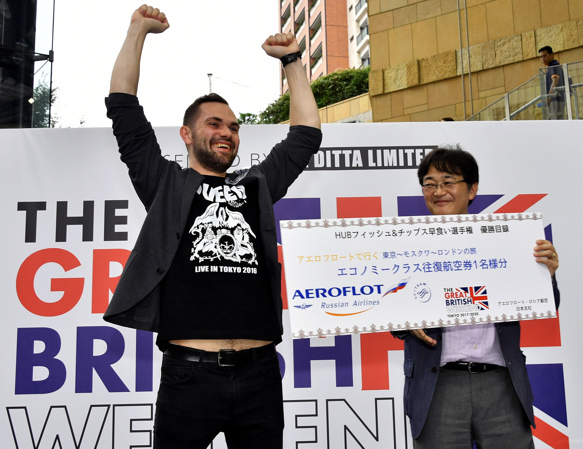 Katsuya Suzuki (right), Aeroflot sales manager for Japan and Australia, presents Fish and Chips Eating Contest winner software engineer Nikolai Egorov with a round-trip airline ticket from Japan to London during The Great British Weekend Tokyo 2017-2020 at Roppongi Hills on Sept. 1. |   YOSHIAKI MIURA